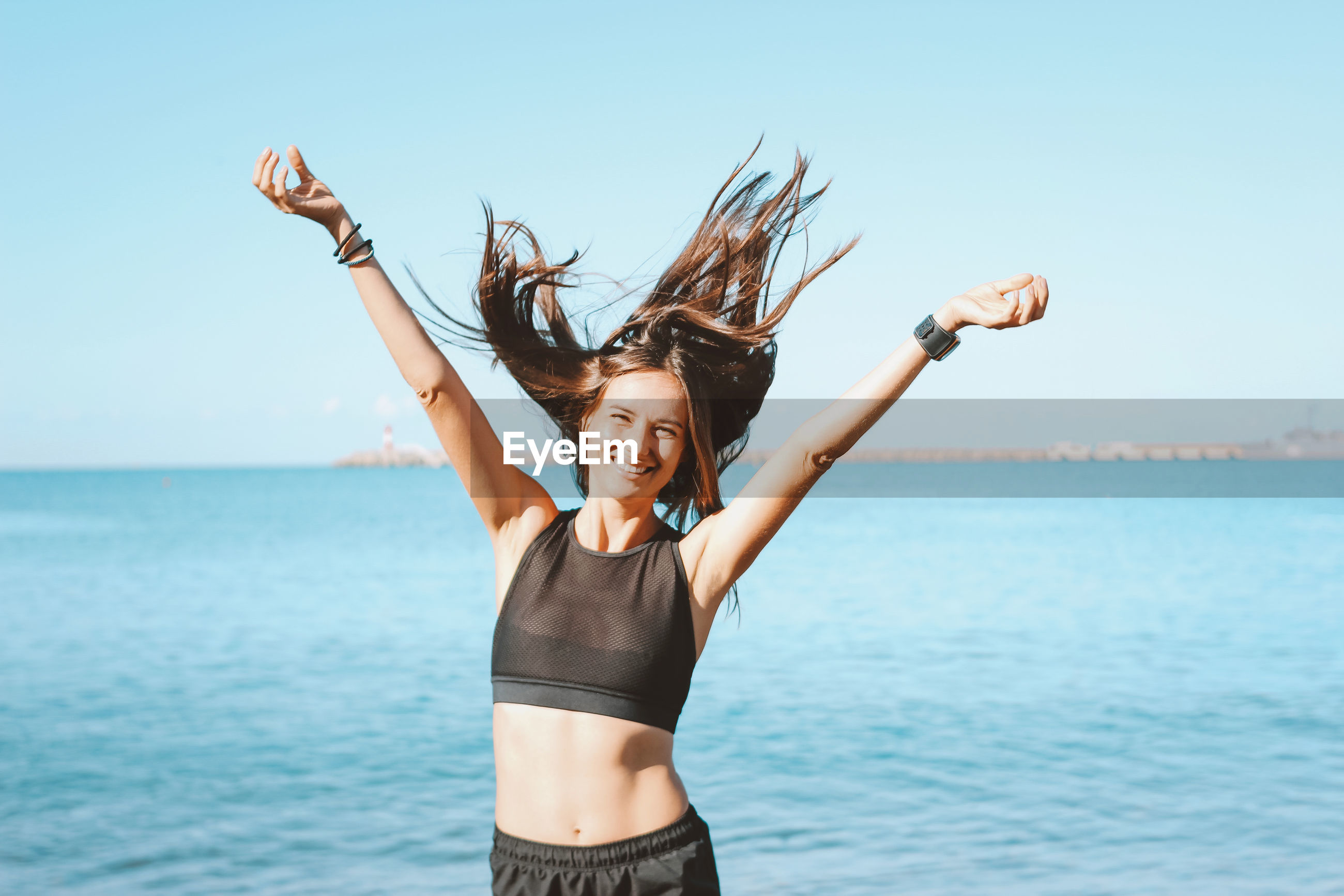 Portrait of woman standing with arms outstretched at beach against sky