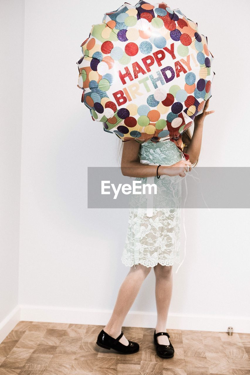 Woman With Inflatable Balloon Standing Against Wall
