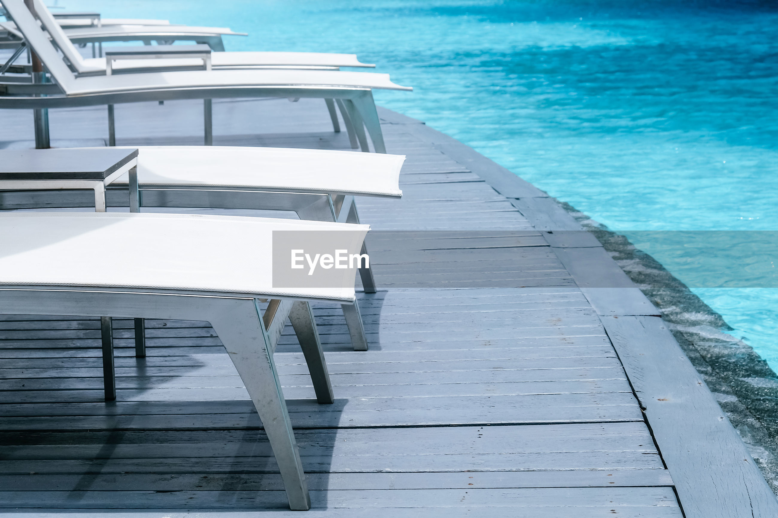HIGH ANGLE VIEW OF EMPTY CHAIRS BY SWIMMING POOL AGAINST SEA