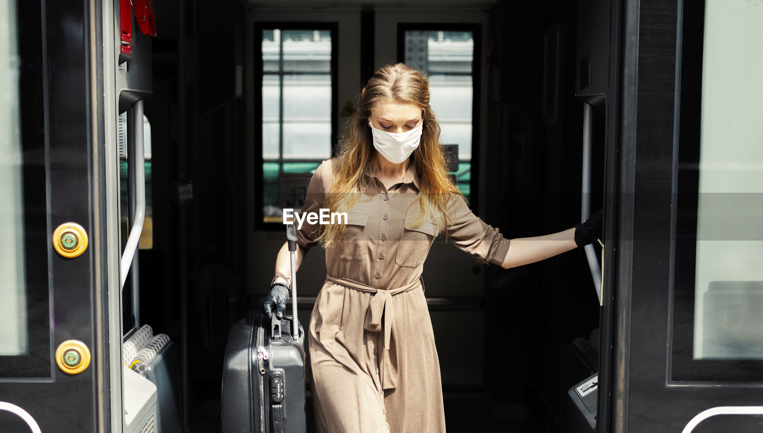 Woman wearing mask with suitcase exiting from train