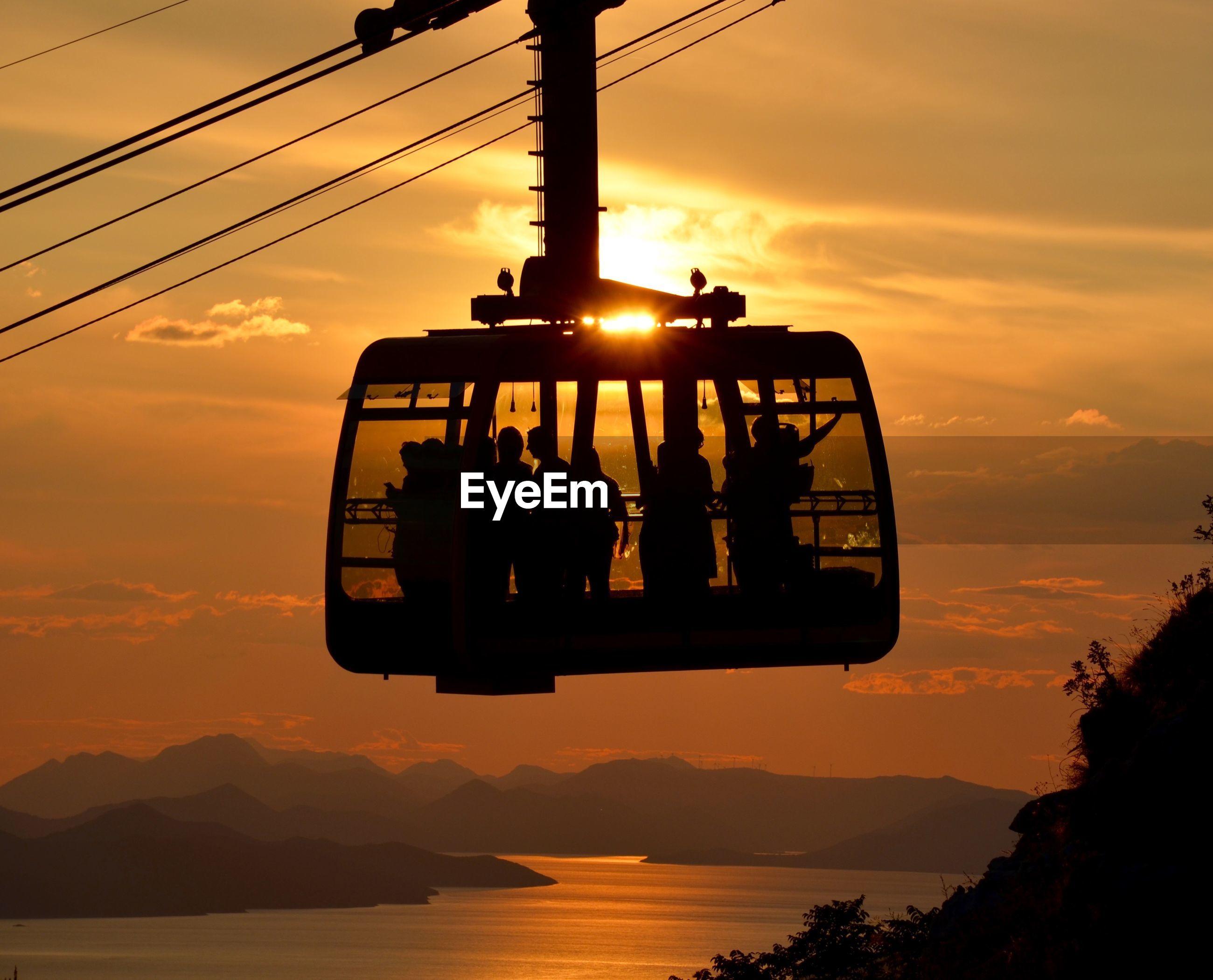 Silhouette people in ferries wheel cabin against sunset
