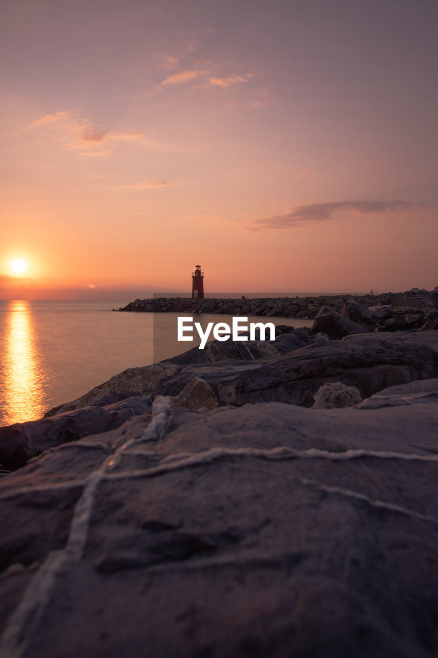 sunset, sky, water, sea, orange color, scenics - nature, beauty in nature, rock, rock - object, solid, tranquility, beach, tranquil scene, land, nature, no people, idyllic, cloud - sky, non-urban scene, horizon over water, outdoors