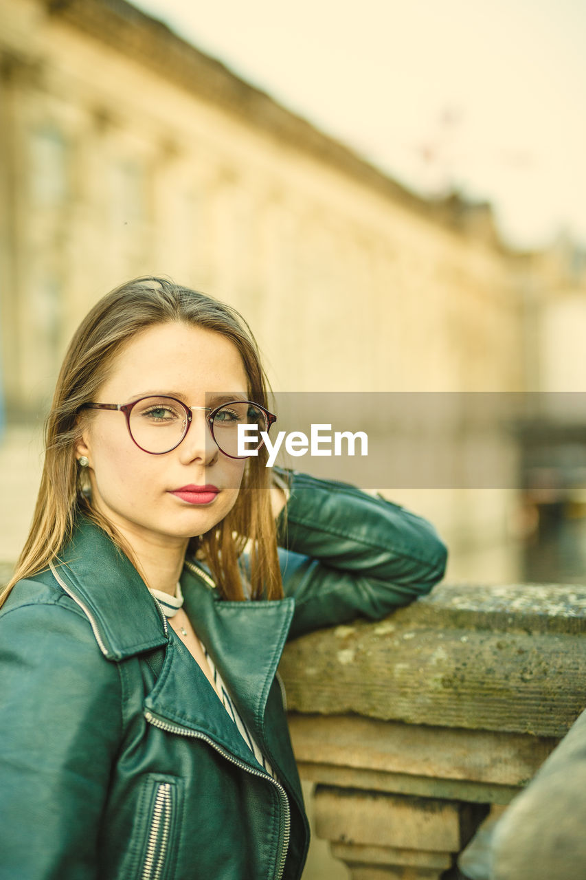 young adult, eyeglasses, portrait, one person, glasses, architecture, real people, front view, young women, lifestyles, looking at camera, leisure activity, built structure, focus on foreground, casual clothing, hair, standing, day, beautiful woman, hairstyle, outdoors