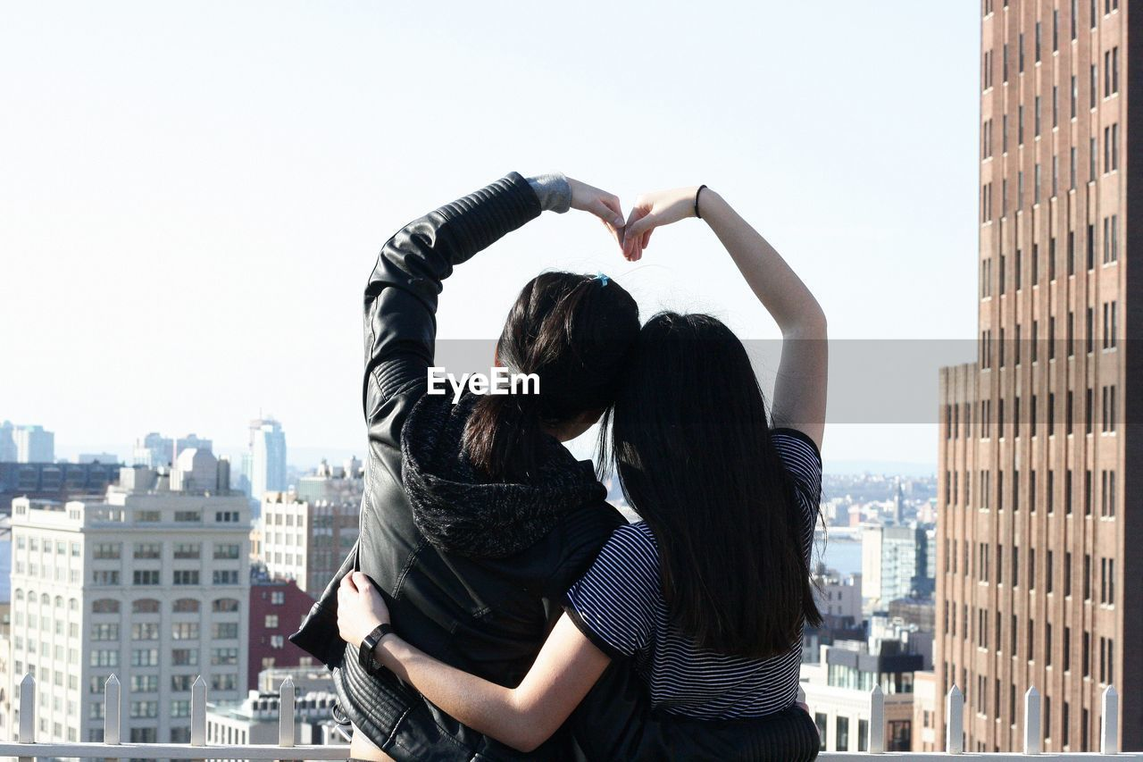 Rear View Of Friends Making Heart Shape In City Against Clear Sky