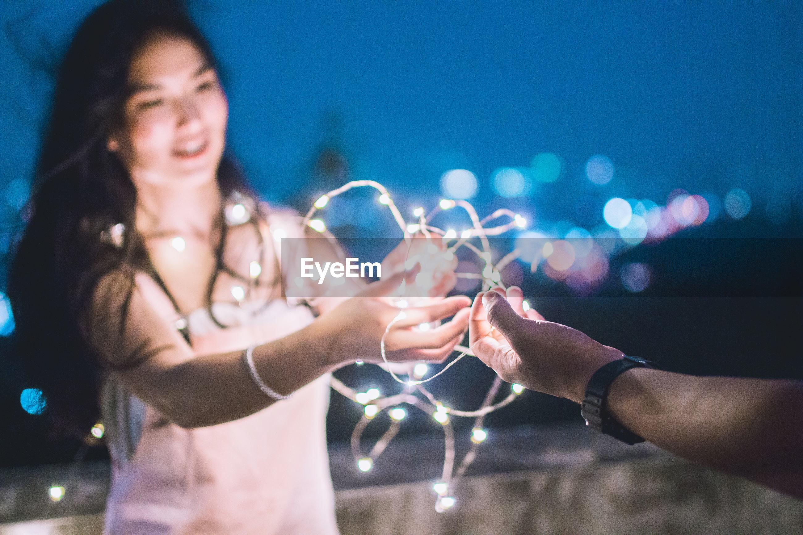 Close-up of couple holding illuminated lights against sky
