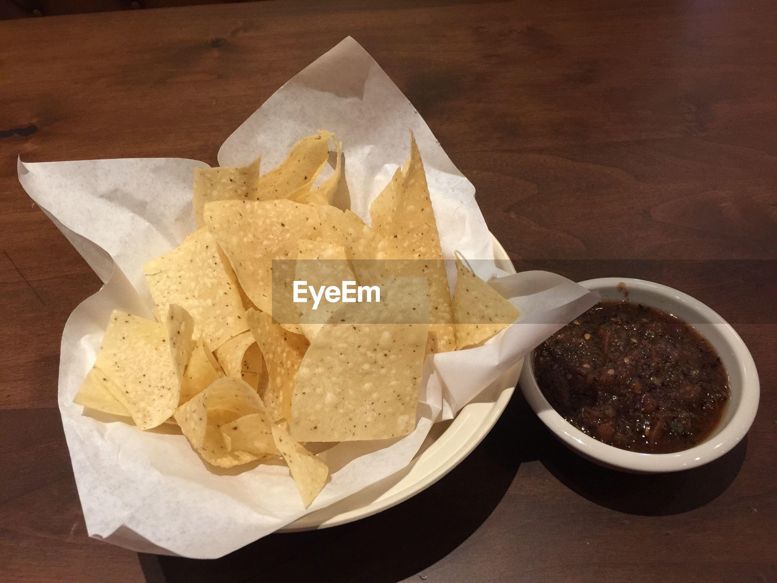 High angle view of nachos and sauce on table