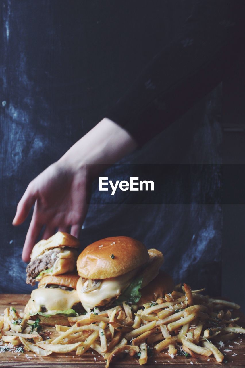 Cropped Hand Of Woman Holding Burgers Over French Fries In Darkroom