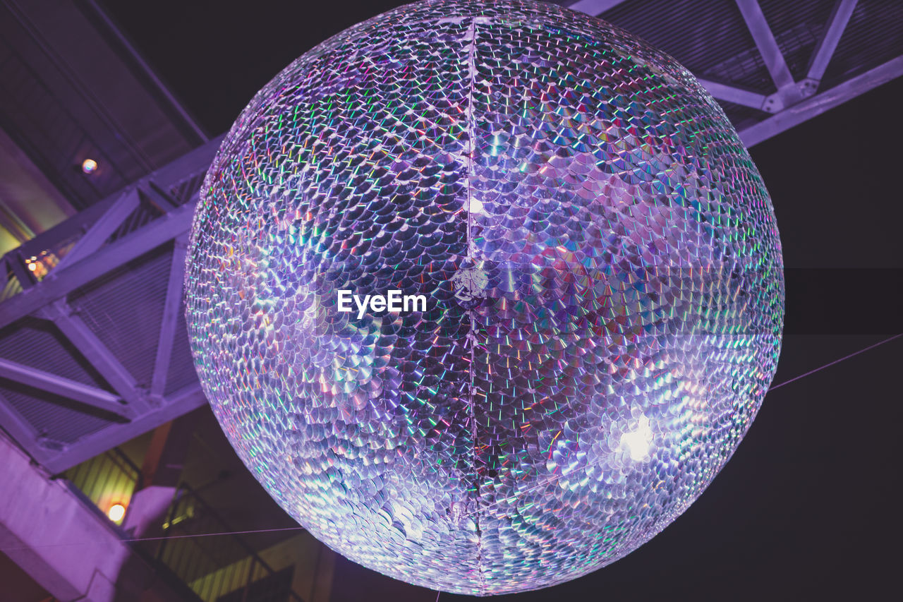 illuminated, sphere, low angle view, decoration, ceiling, lighting equipment, night, pattern, hanging, no people, indoors, design, multi colored, disco ball, geometric shape, shape, celebration, glowing, circle, built structure, light, nightlife, purple