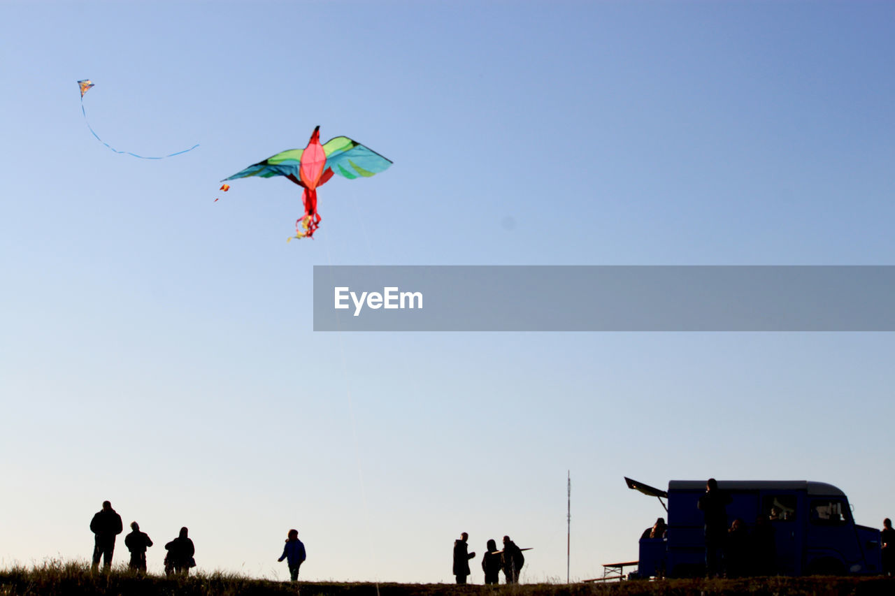sky, flying, clear sky, leisure activity, nature, copy space, men, motion, people, group of people, low angle view, mid-air, real people, day, kite - toy, lifestyles, outdoors, adult, medium group of people, land