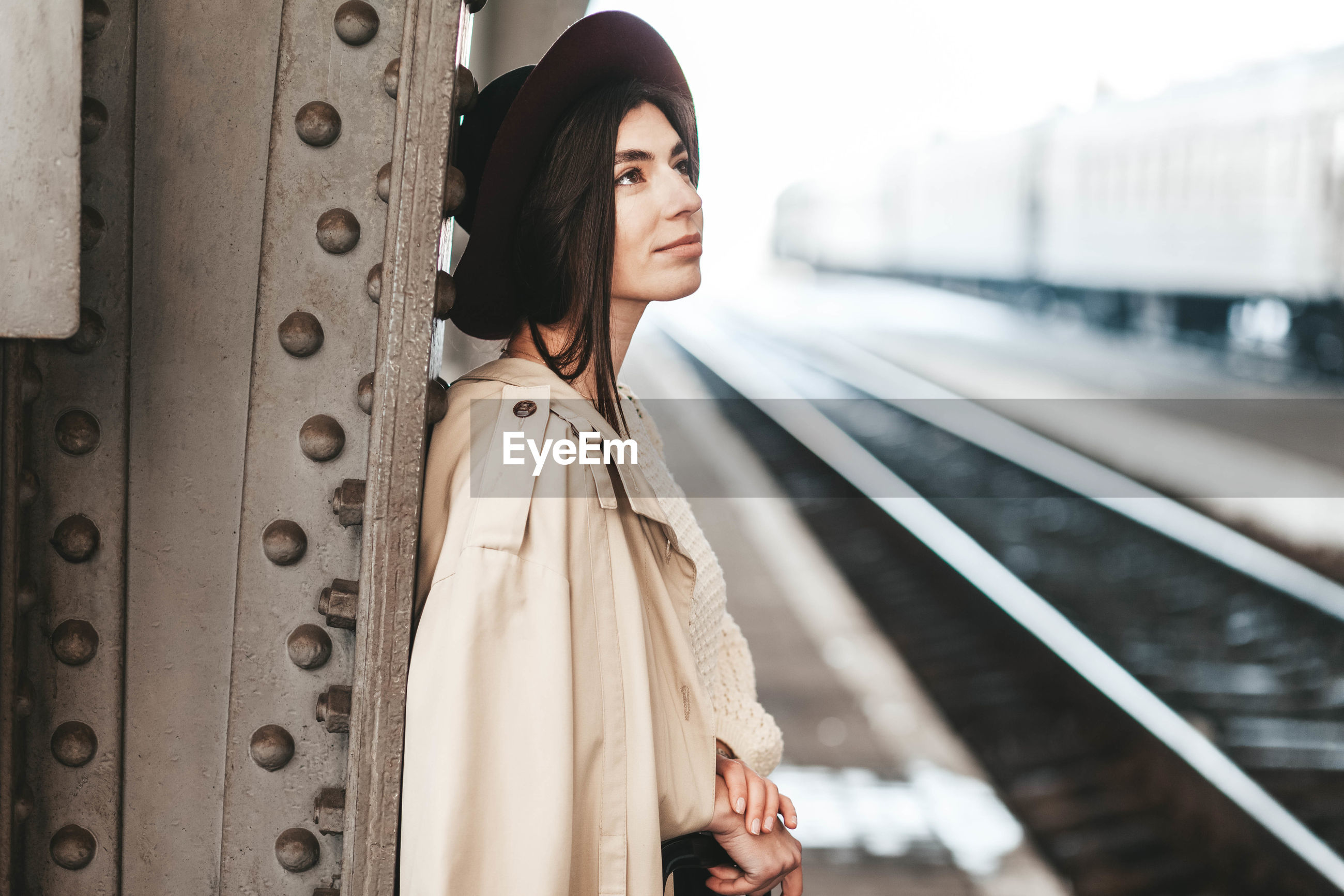 FULL LENGTH OF YOUNG WOMAN STANDING ON RAILROAD STATION
