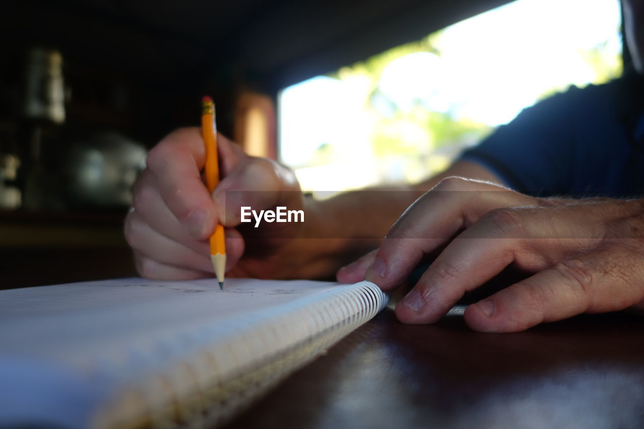 Cropped Hands Of Man Writing On Book