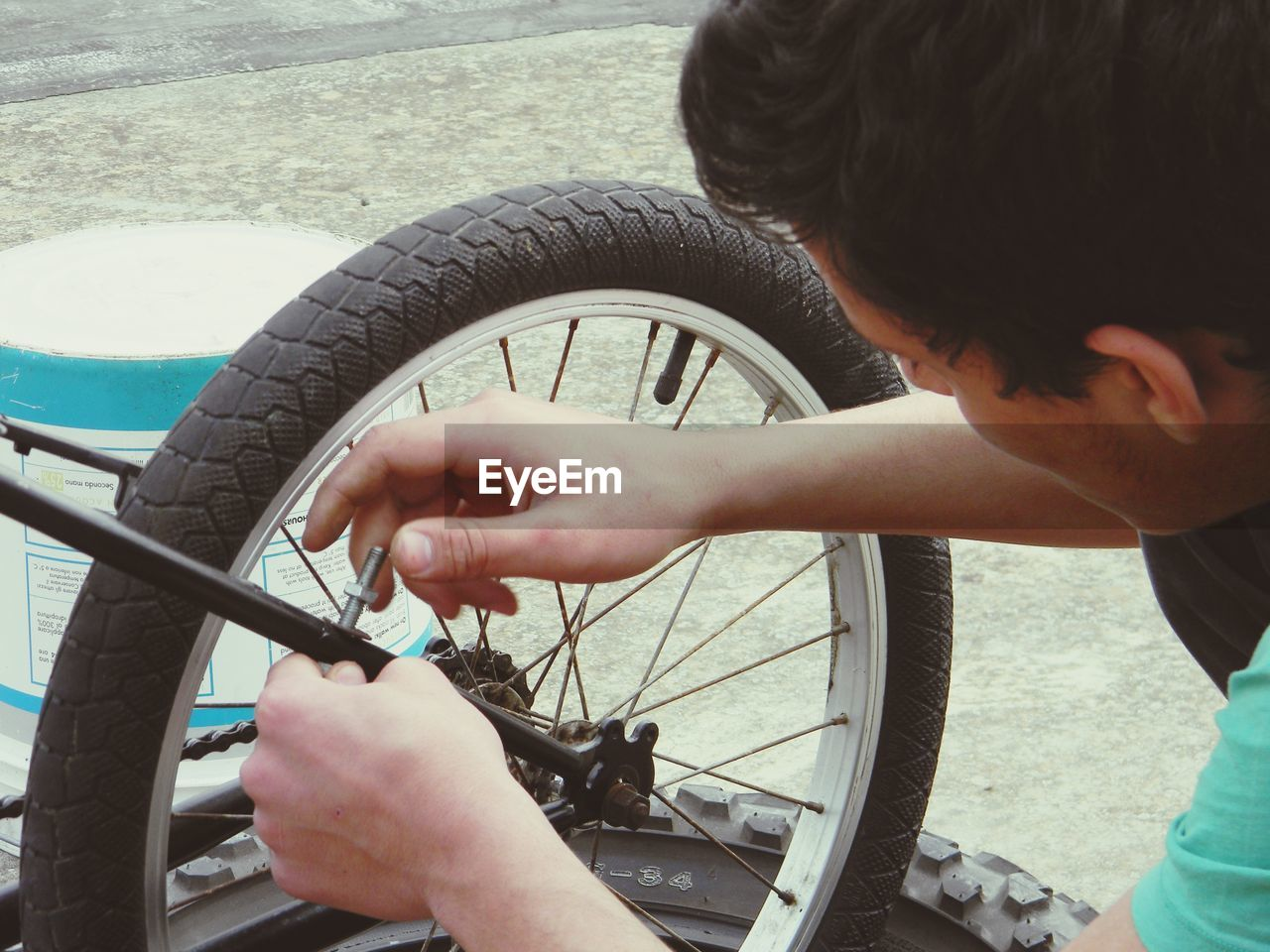 Young Man Repairing Bicycle Outdoors