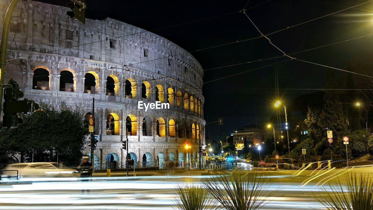 Illuminated light trails by coliseum at night