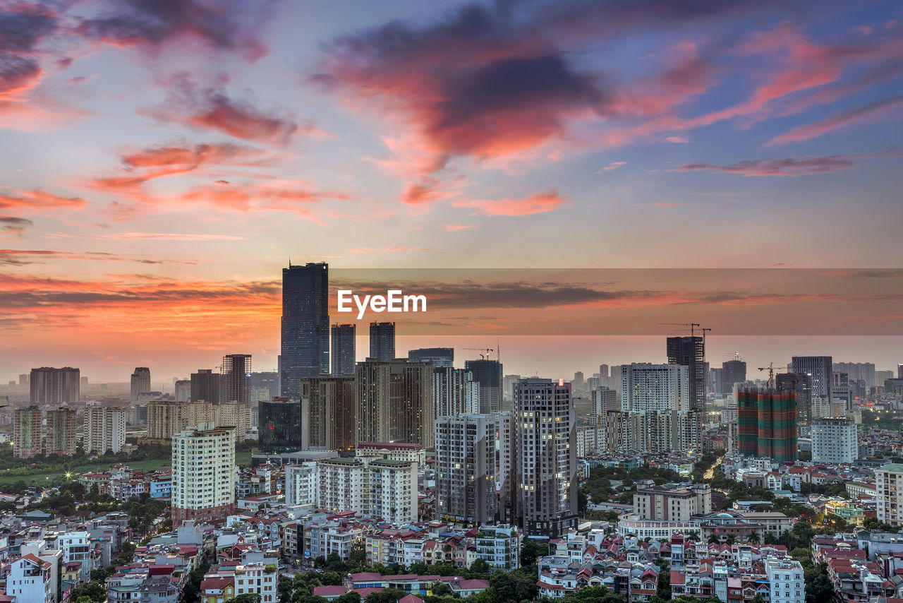 architecture, building exterior, sky, sunset, city, built structure, building, cityscape, office building exterior, orange color, cloud - sky, skyscraper, tall - high, crowd, residential district, nature, urban skyline, modern, crowded, outdoors, financial district, romantic sky, settlement