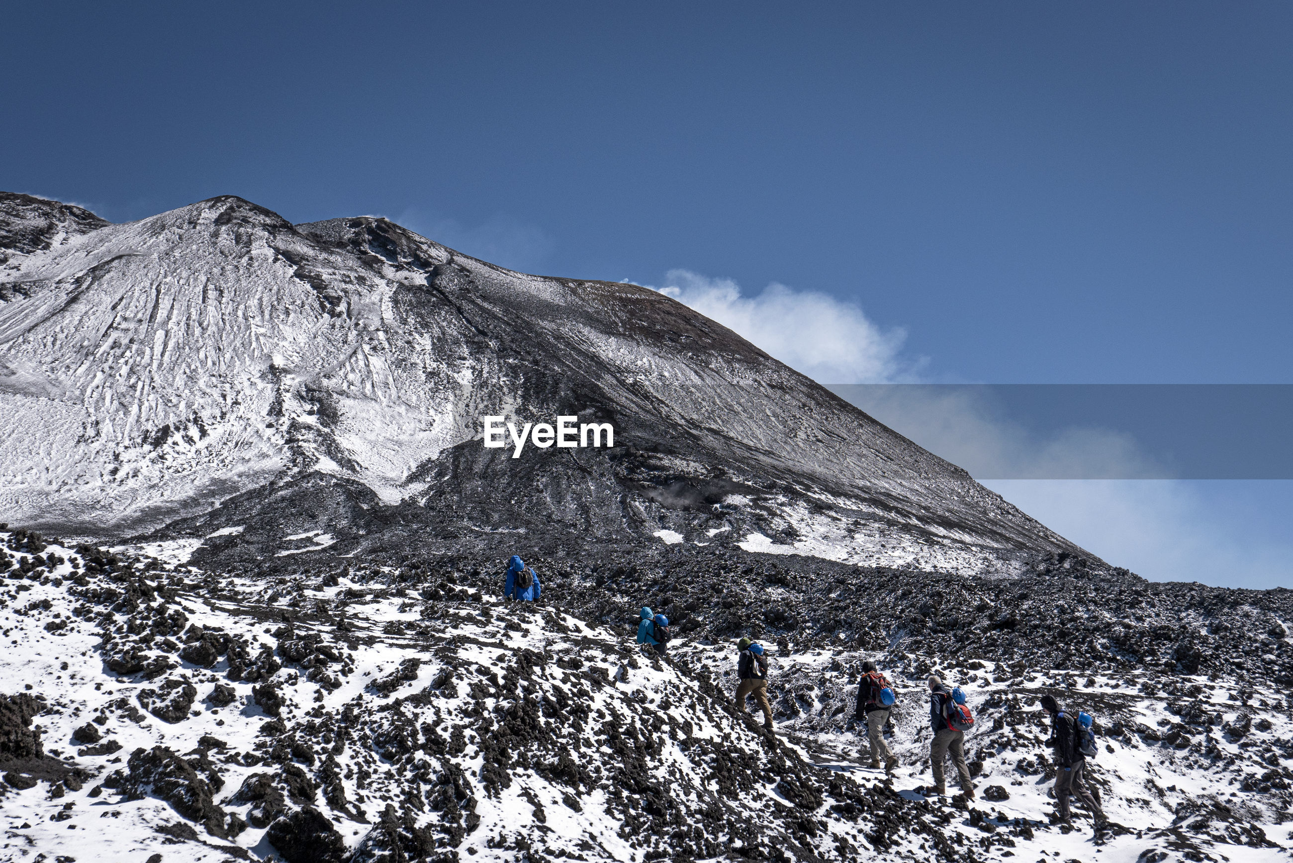 PEOPLE ON SNOWCAPPED MOUNTAINS AGAINST SKY