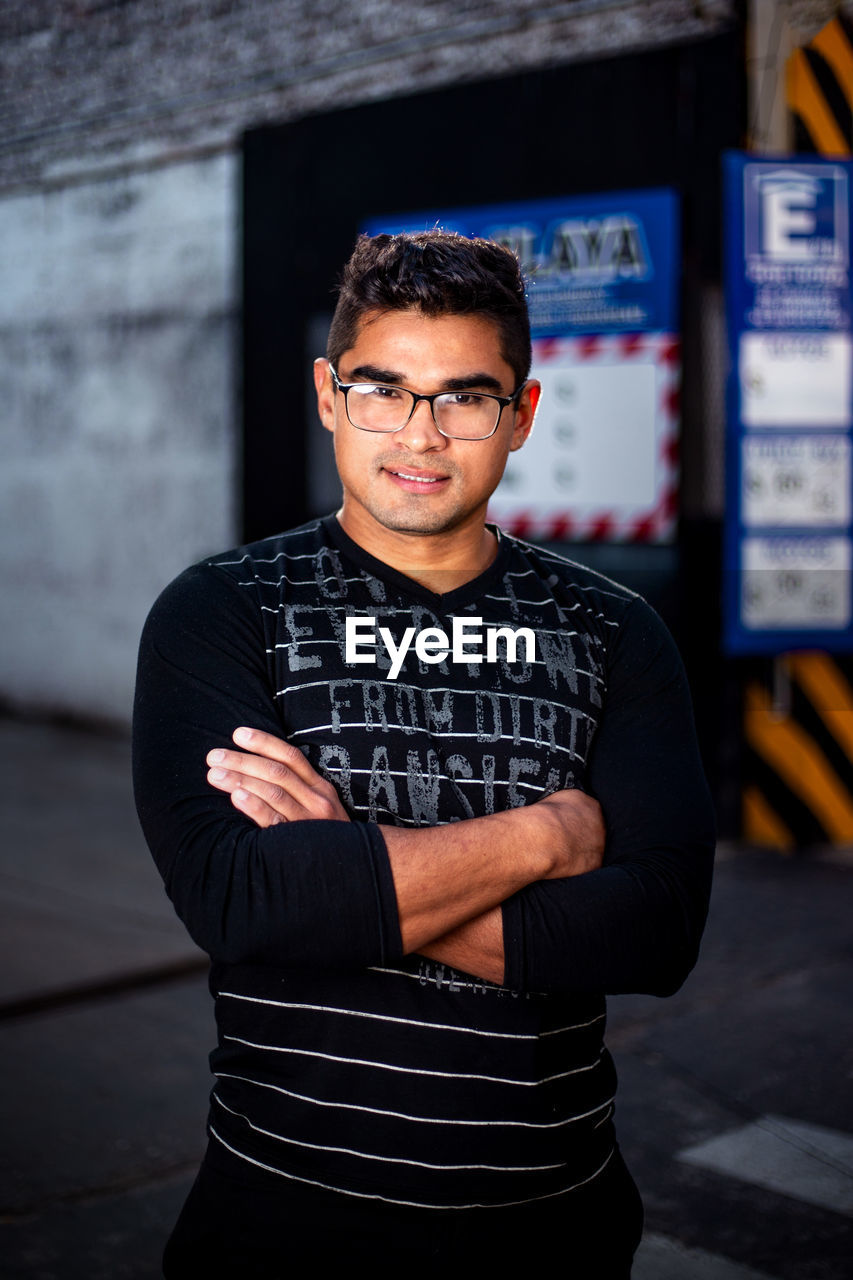 looking at camera, portrait, front view, one person, young adult, young men, real people, eyeglasses, glasses, standing, casual clothing, waist up, lifestyles, focus on foreground, leisure activity, males, arms crossed, indoors