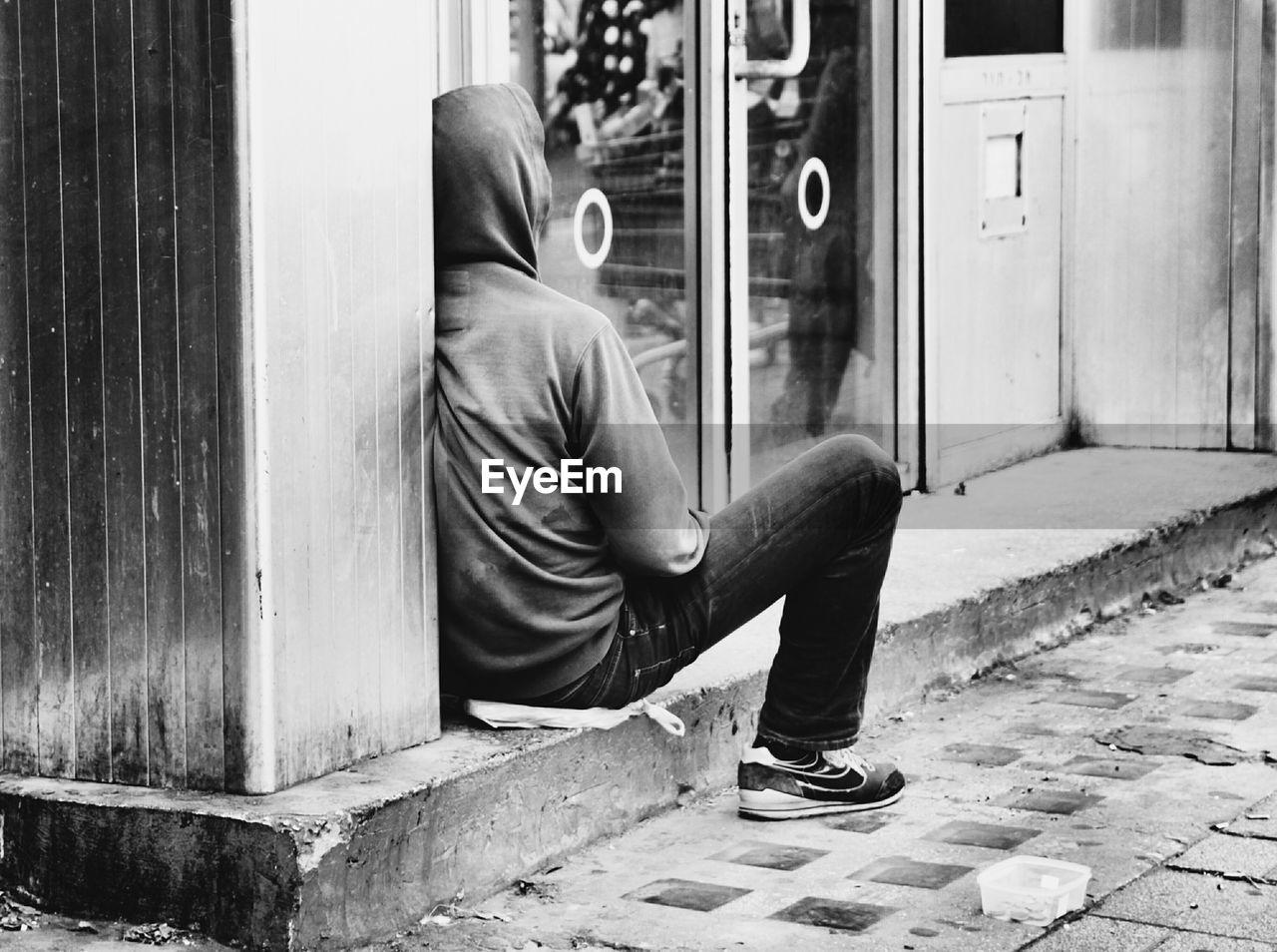 Man Wearing Hooded Shirt Sitting Outside Shop