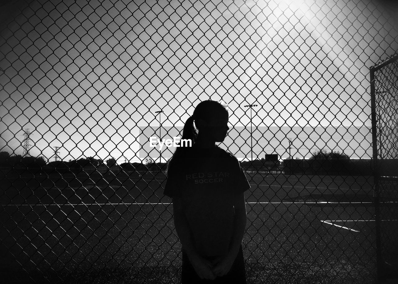 chainlink fence, baseball - sport, real people, standing, sport, rear view, baseball player, playing field, childhood, team sport, one person, playing, outdoors, baseball bat, day, nature, baseball helmet, sky, people