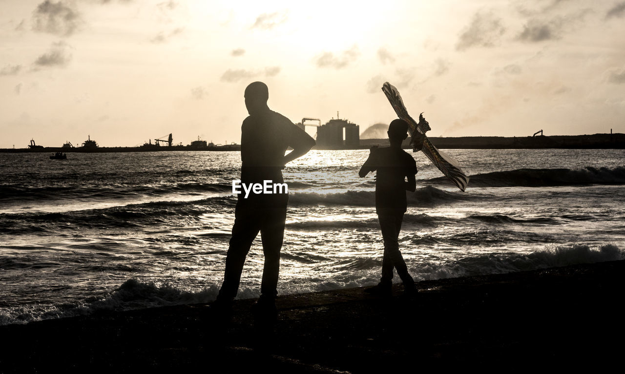 water, sea, sky, beach, real people, men, two people, land, silhouette, sunset, beauty in nature, leisure activity, nature, lifestyles, togetherness, people, standing, horizon over water, horizon, outdoors