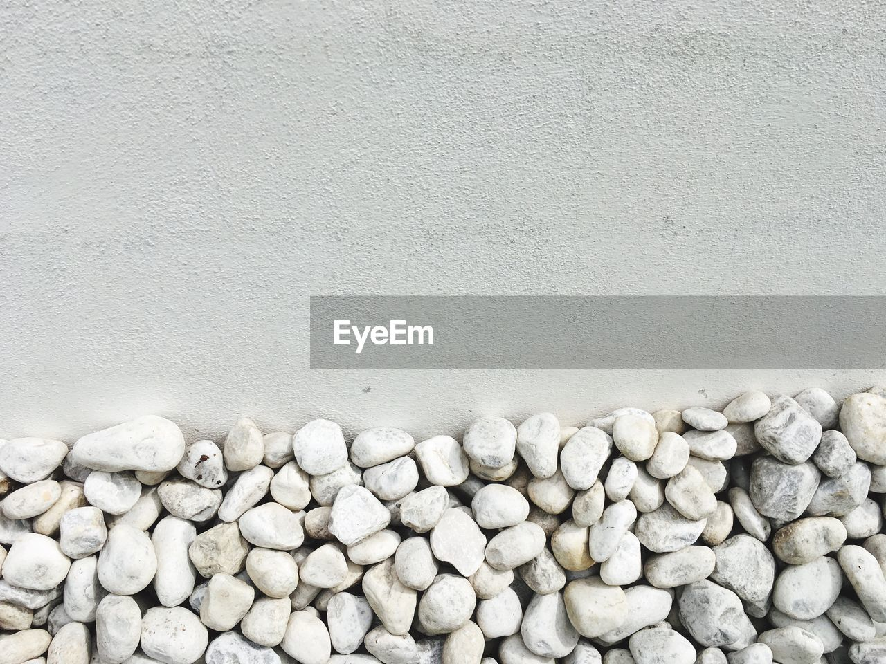 Pebbles Against White Concrete Wall