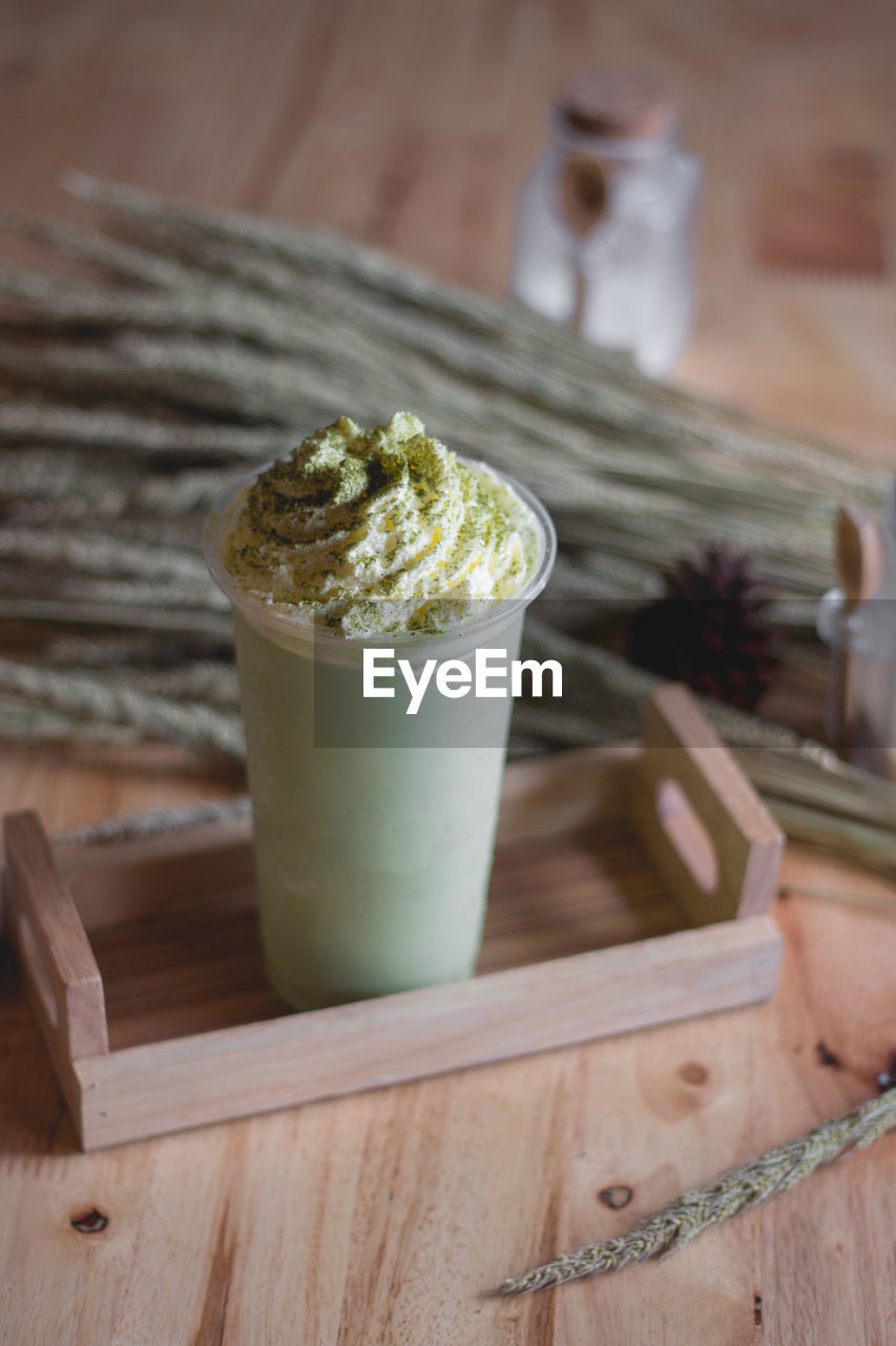food and drink, wood - material, food, indoors, still life, table, no people, drink, focus on foreground, cup, close-up, freshness, indulgence, refreshment, coffee - drink, green color, coffee, potted plant, mug, serving size, latte, glass, temptation