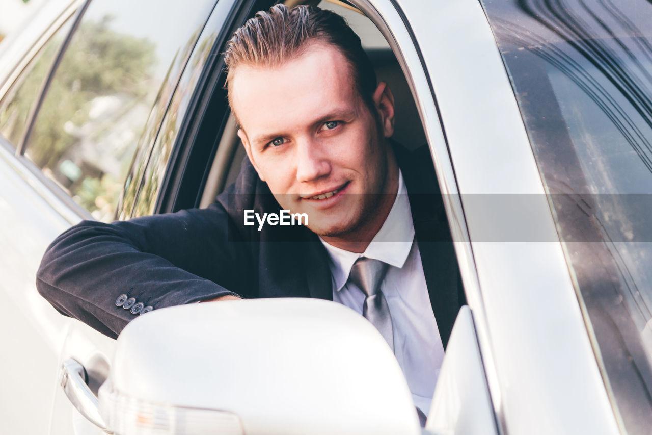 Portrait of businessman driving car