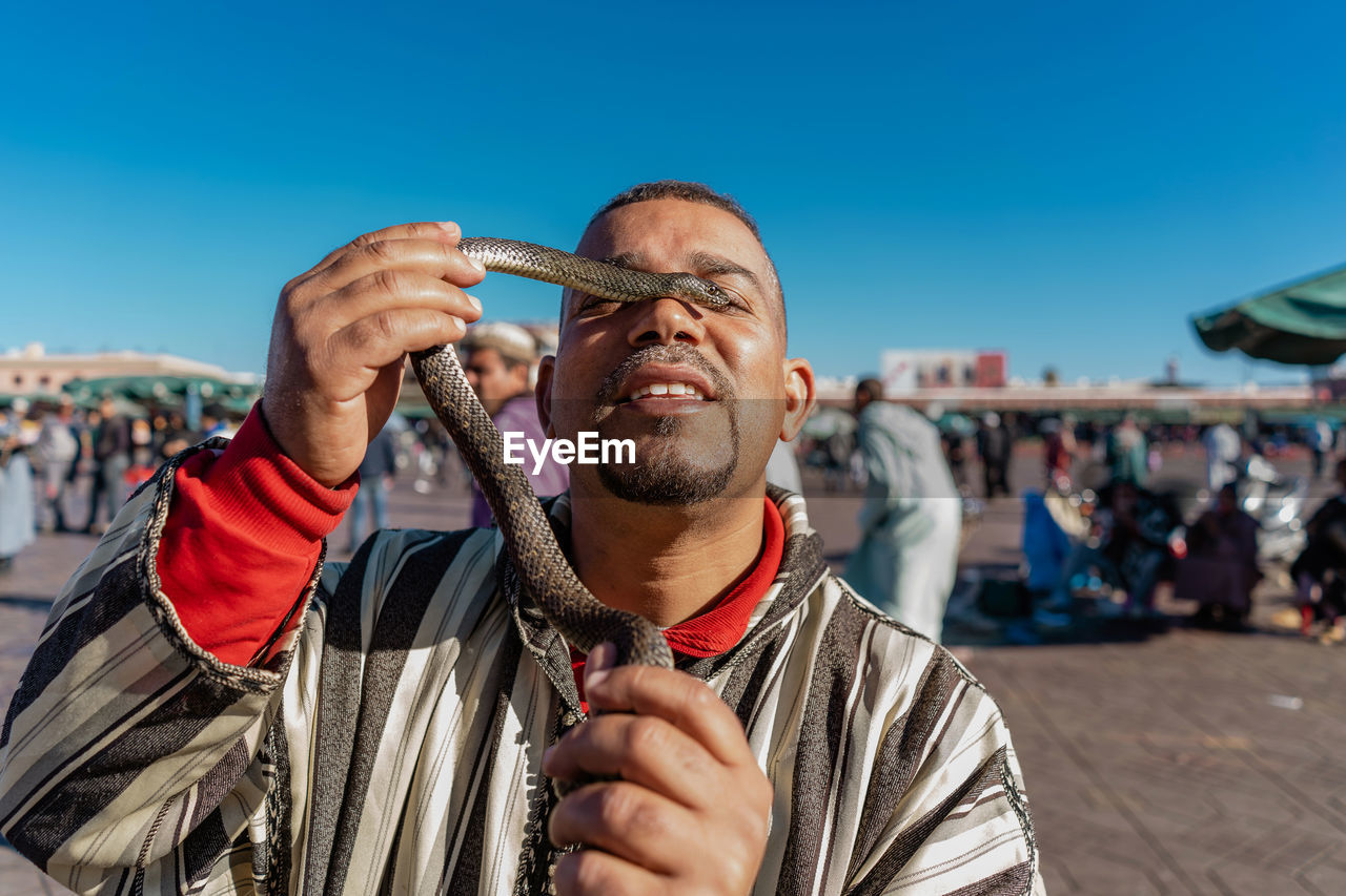 front view, one person, men, holding, real people, sky, lifestyles, males, sunlight, leisure activity, portrait, casual clothing, incidental people, mature men, focus on foreground, headshot, day, mature adult, outdoors