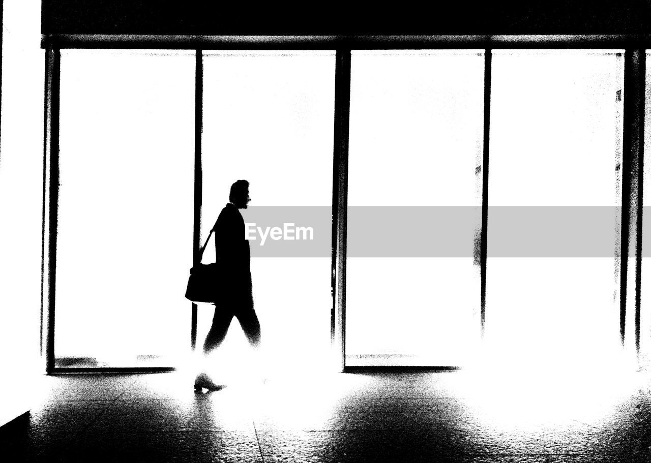 SILHOUETTE MAN STANDING BY BUILDING