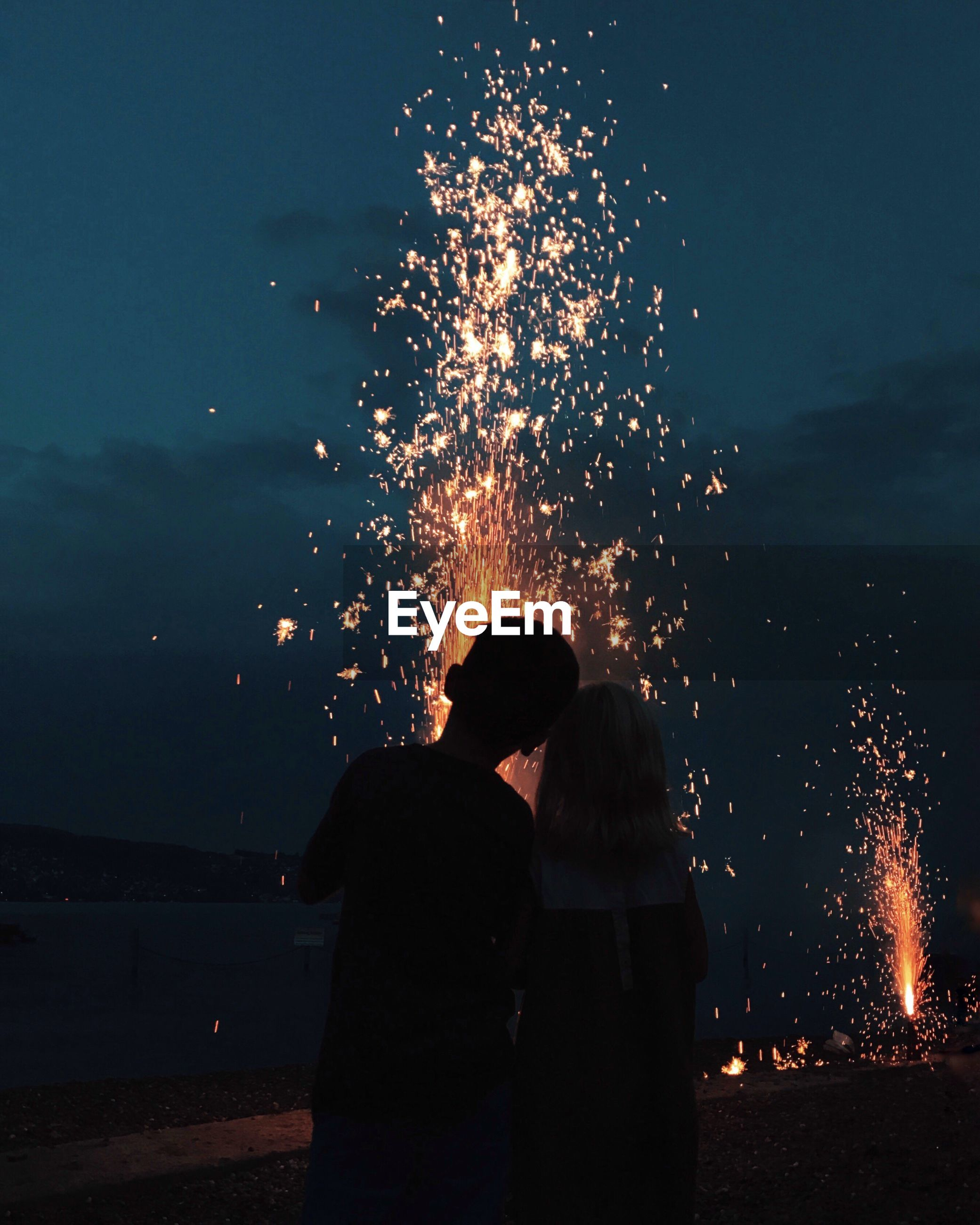 Man and woman looking at firework display against sky