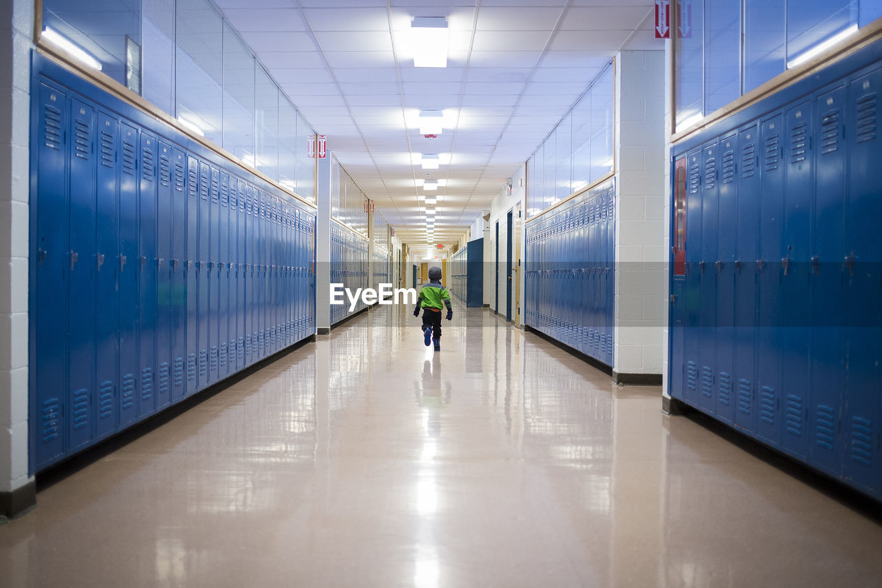 illuminated, indoors, architecture, direction, rear view, the way forward, real people, lighting equipment, transportation, one person, walking, public transportation, full length, men, travel, flooring, lifestyles, diminishing perspective, corridor, ceiling