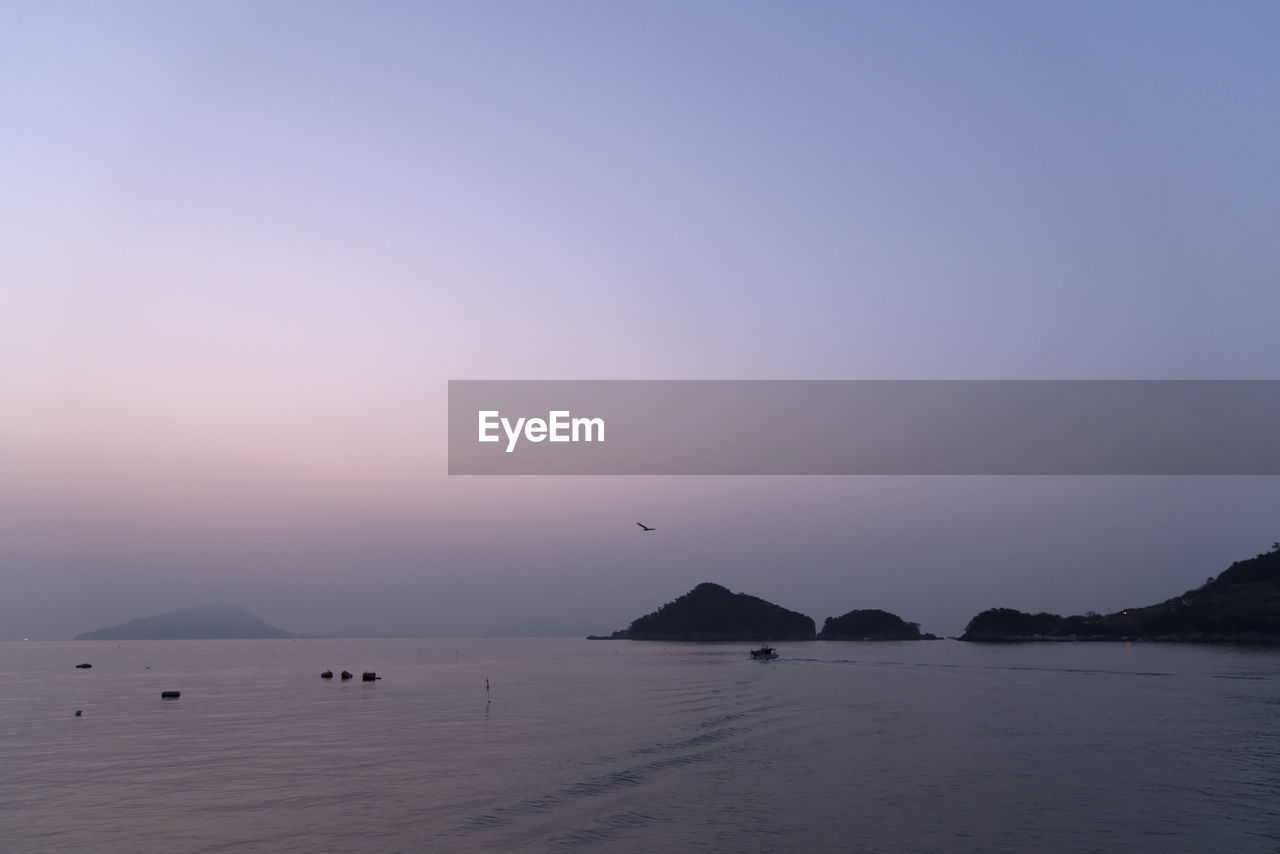 scenics - nature, sky, water, beauty in nature, tranquil scene, sea, tranquility, copy space, nature, waterfront, sunset, idyllic, no people, mountain, non-urban scene, silhouette, clear sky, outdoors, blue