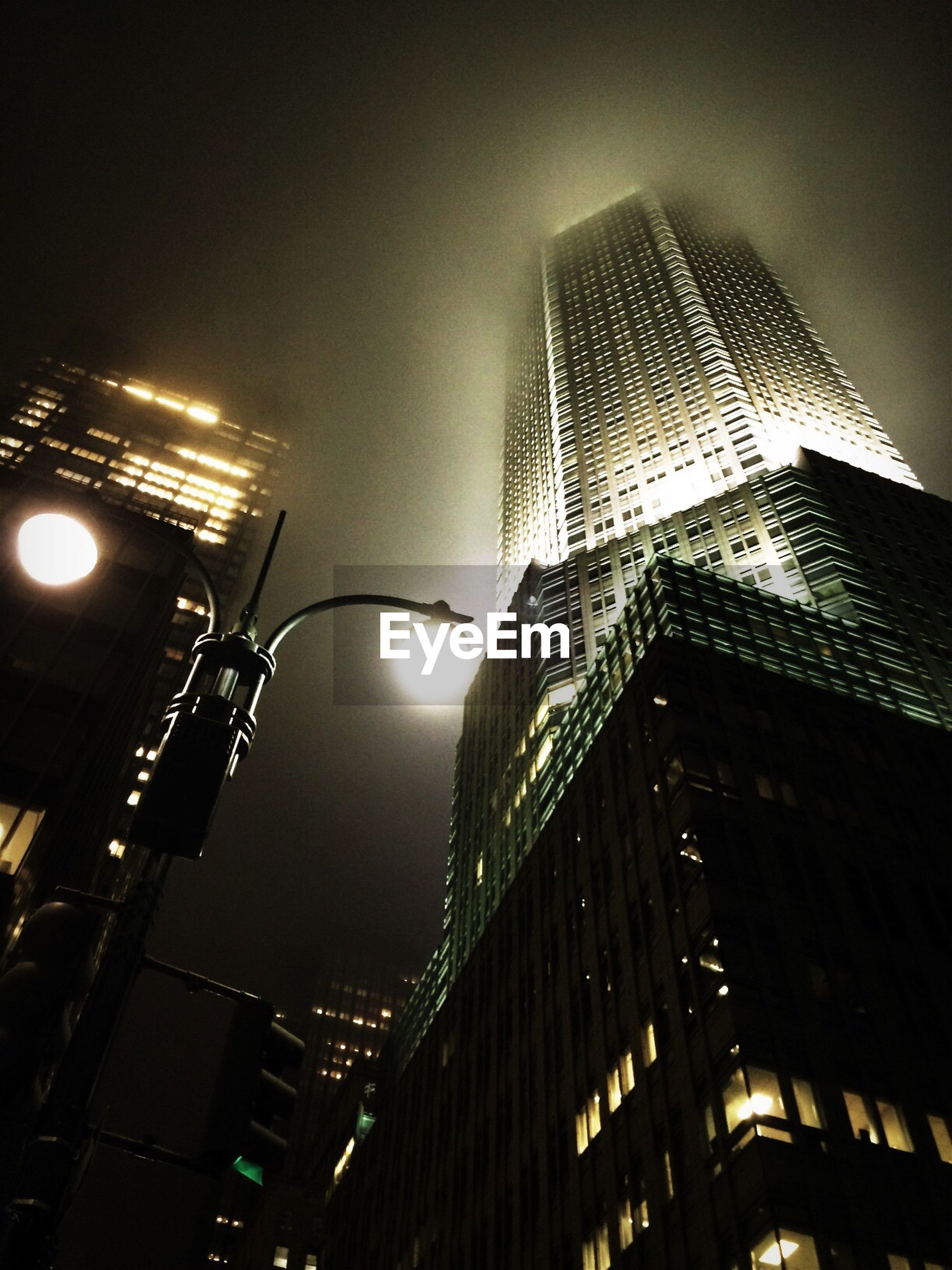 Low angle view of illuminated tower at night during foggy weather