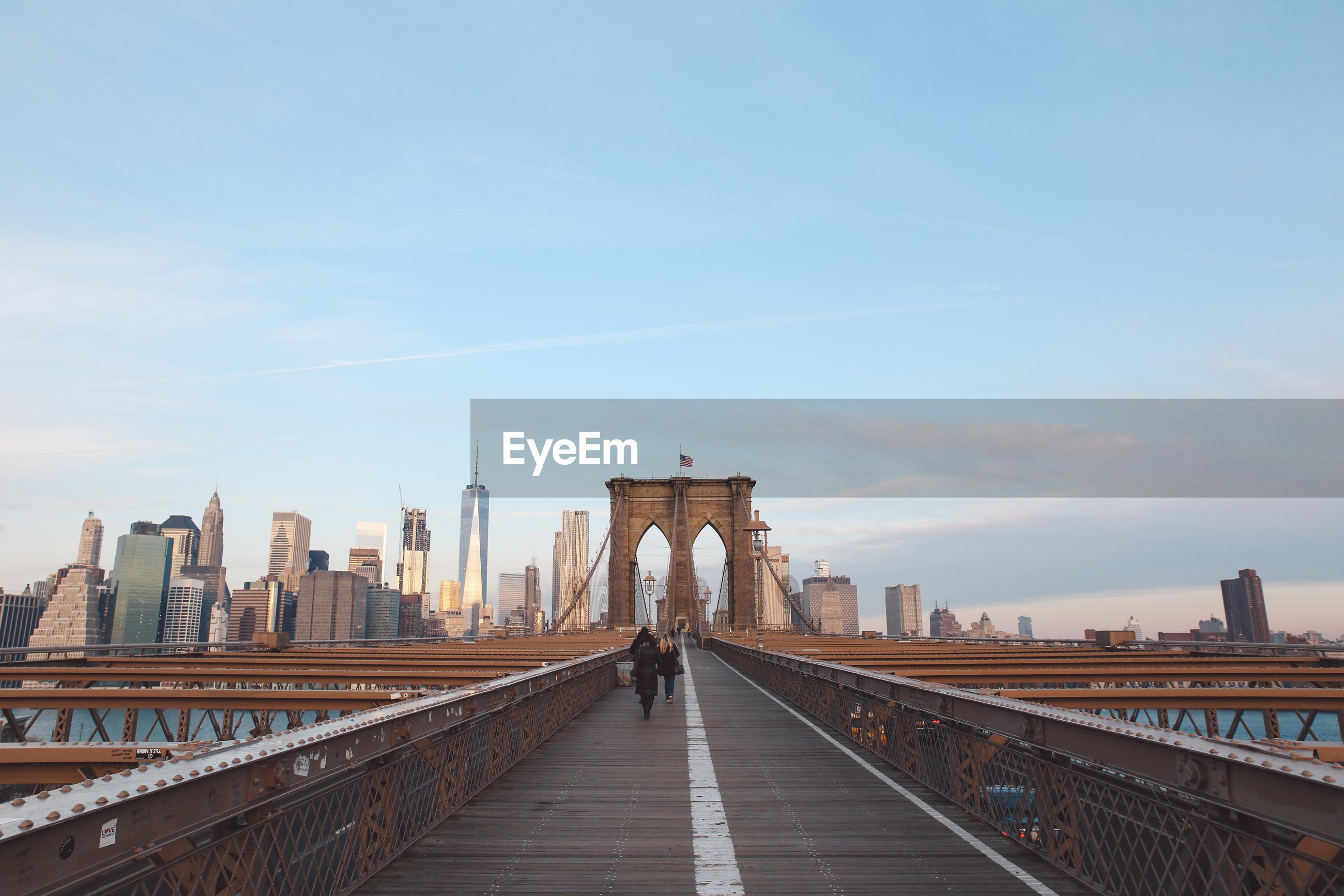 People walking on brooklyn bridge against sky in city
