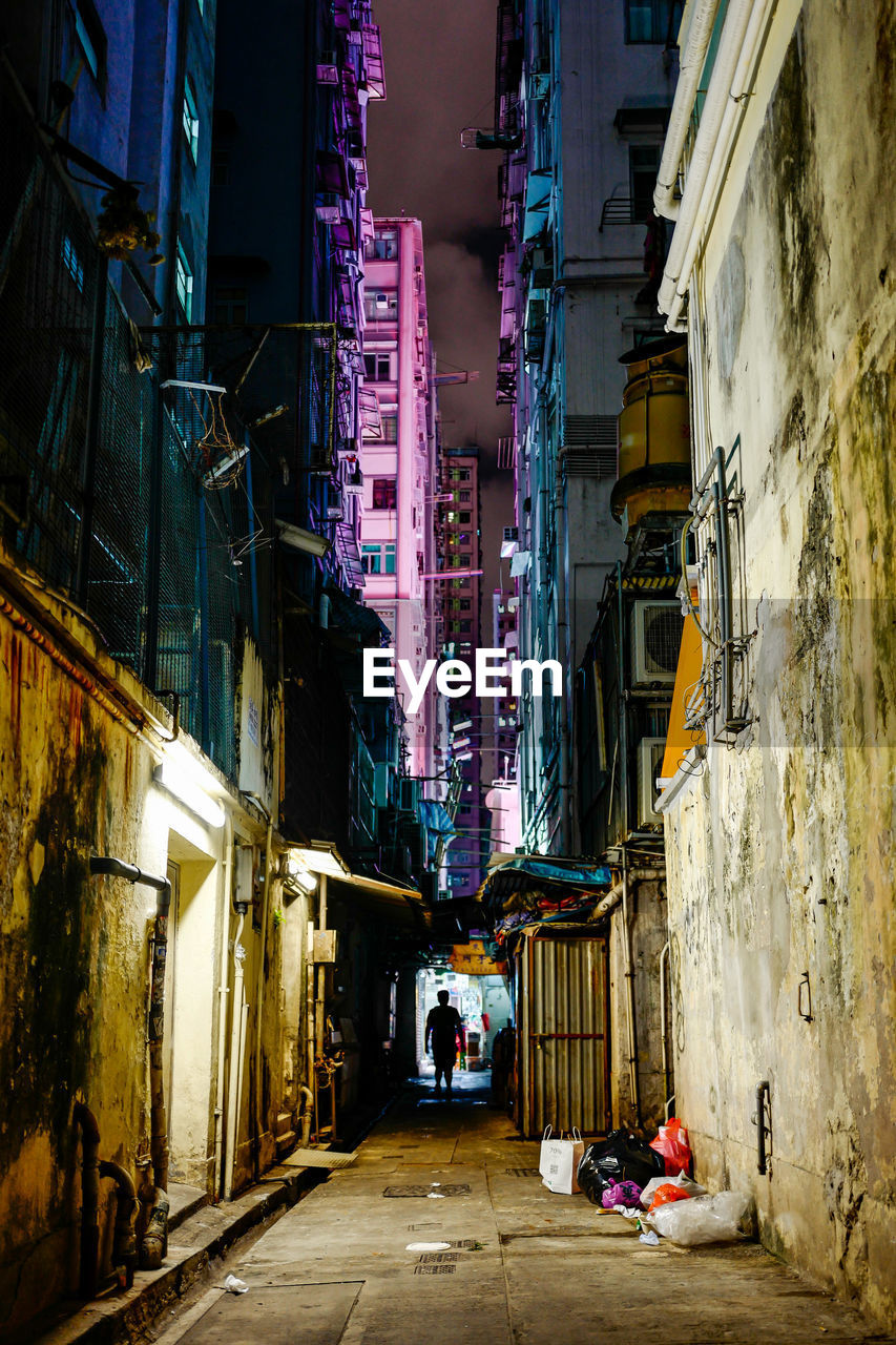 building exterior, architecture, built structure, city, building, real people, direction, residential district, alley, the way forward, street, illuminated, lifestyles, group of people, walking, narrow, night, people, lighting equipment, men, outdoors