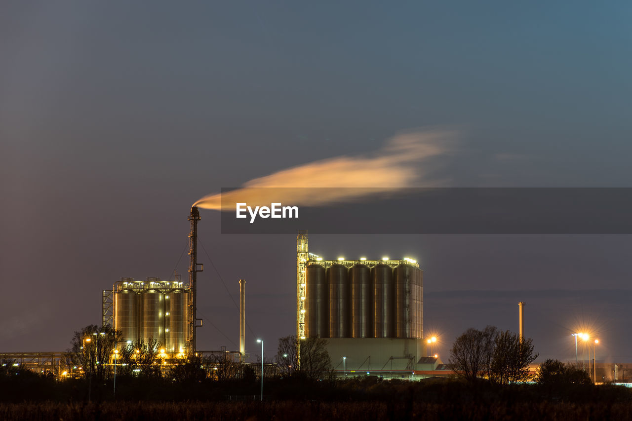building exterior, sky, built structure, illuminated, industry, architecture, factory, fuel and power generation, night, no people, nature, cloud - sky, industrial building, smoke stack, environmental issues, outdoors, pollution, smoke - physical structure, tall - high, glowing, air pollution, industrial equipment