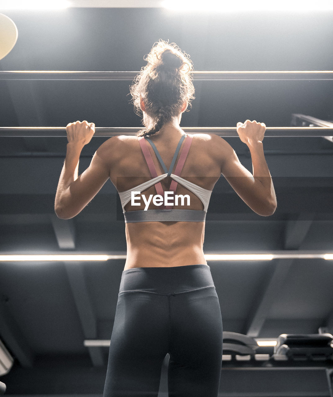 rear view, one person, clothing, lifestyles, three quarter length, sports clothing, healthy lifestyle, real people, sport, exercising, adult, muscular build, indoors, young adult, standing, leisure activity, young women, determination, women, hairstyle, human arm, beautiful woman, body part, arms raised