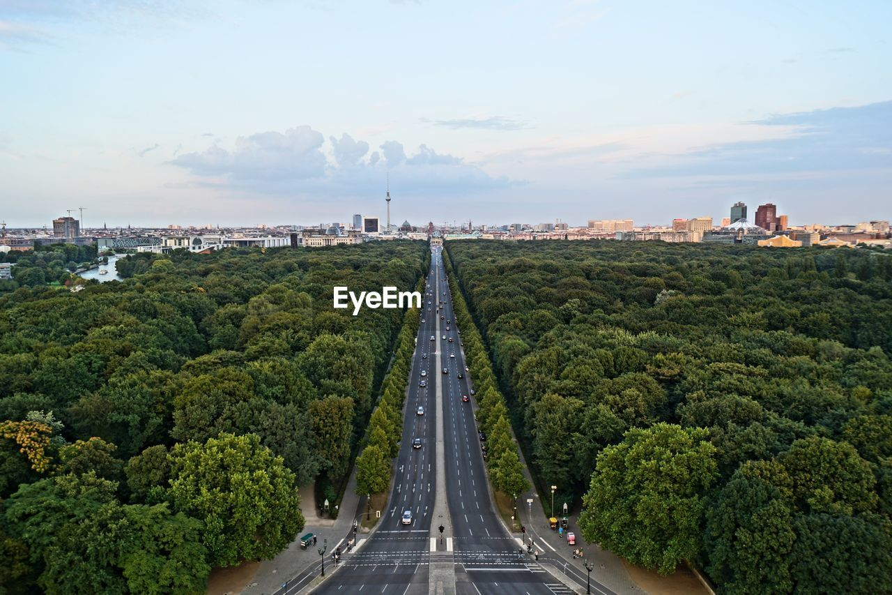 Street Amidst Trees Leading Towards City Against Sky