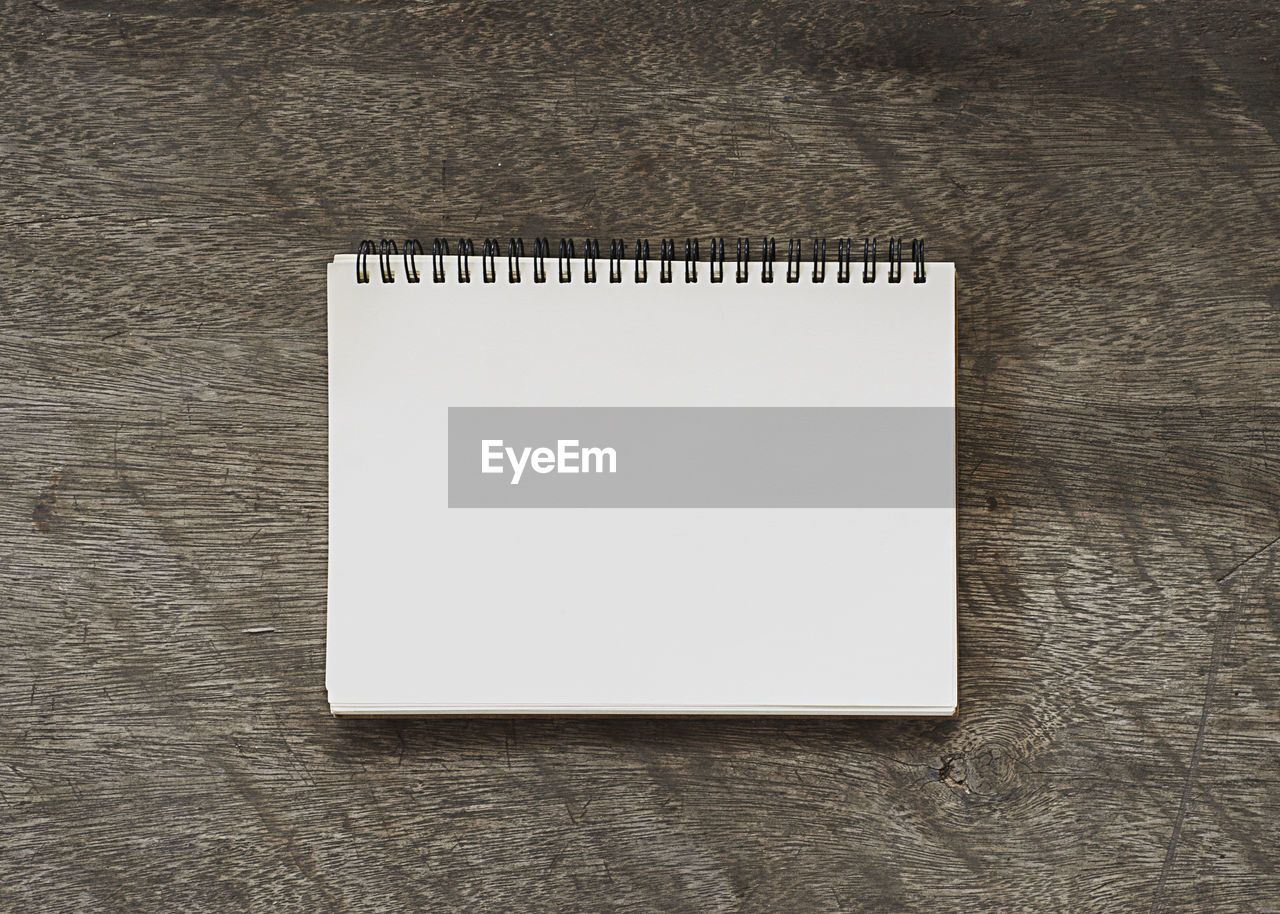 copy space, indoors, no people, note pad, table, paper, blank, wood - material, high angle view, simplicity, close-up, spiral notebook, directly above, white color, still life, textured, office, empty, single object, message, clean, wood grain
