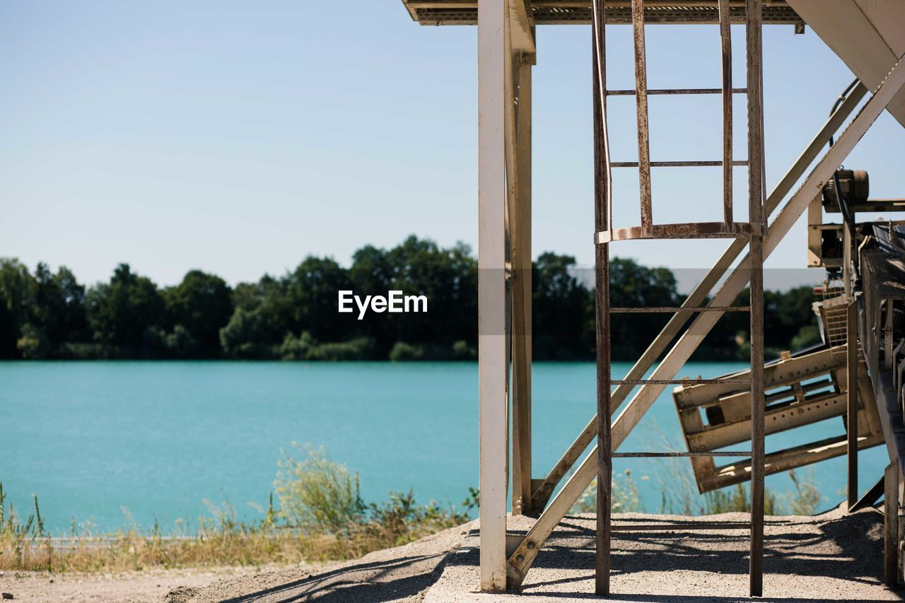 water, sky, tree, nature, focus on foreground, day, no people, plant, wood - material, clear sky, lake, sunlight, built structure, outdoors, architecture, metal, tranquility, land, ladder, swimming pool