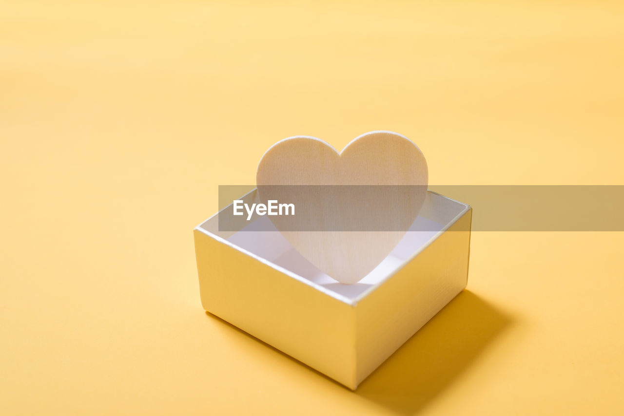 Close-up of heart shape in box on yellow background