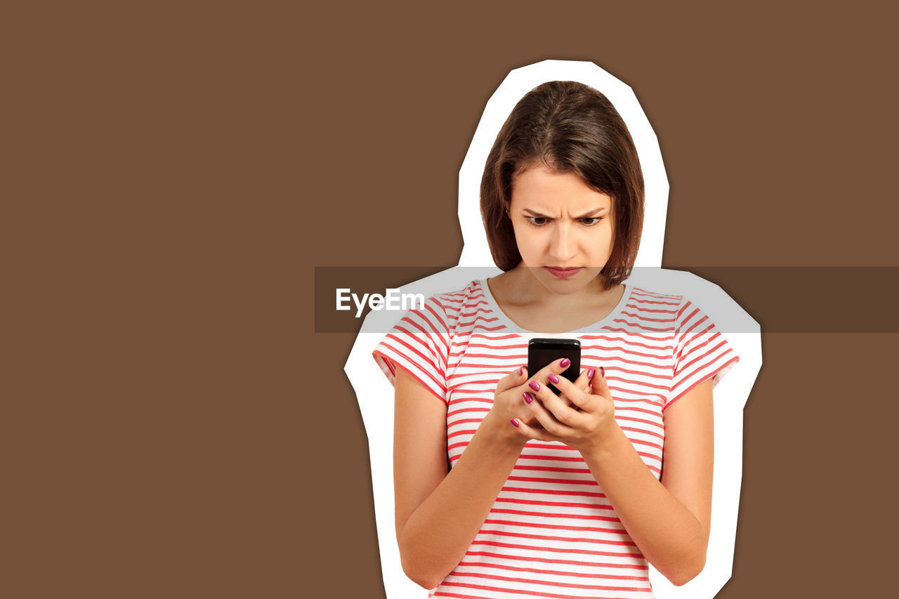Young woman using mobile phone against brown background