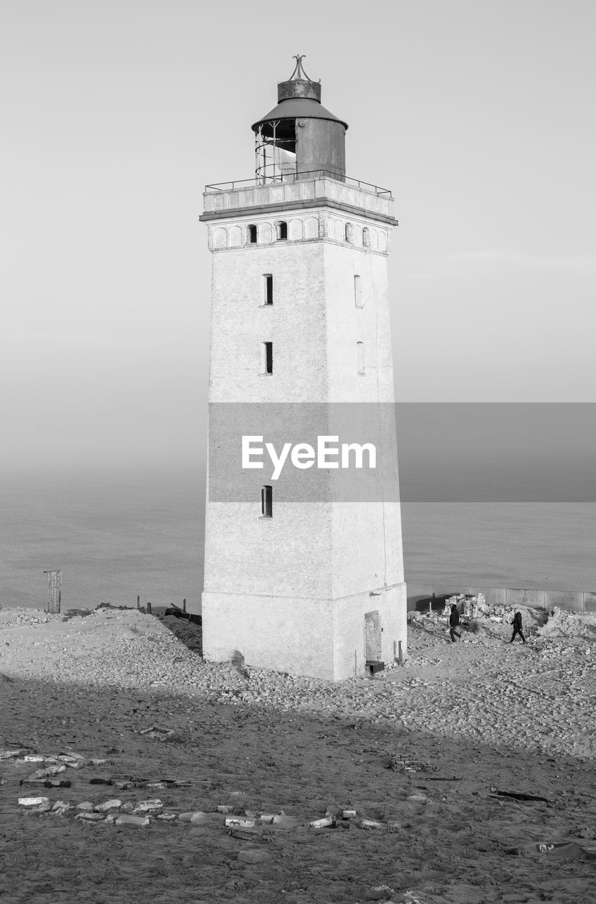 tower, built structure, lighthouse, architecture, sea, sky, building exterior, land, water, building, beach, security, safety, nature, protection, guidance, travel, day, history, outdoors, horizon over water, no people