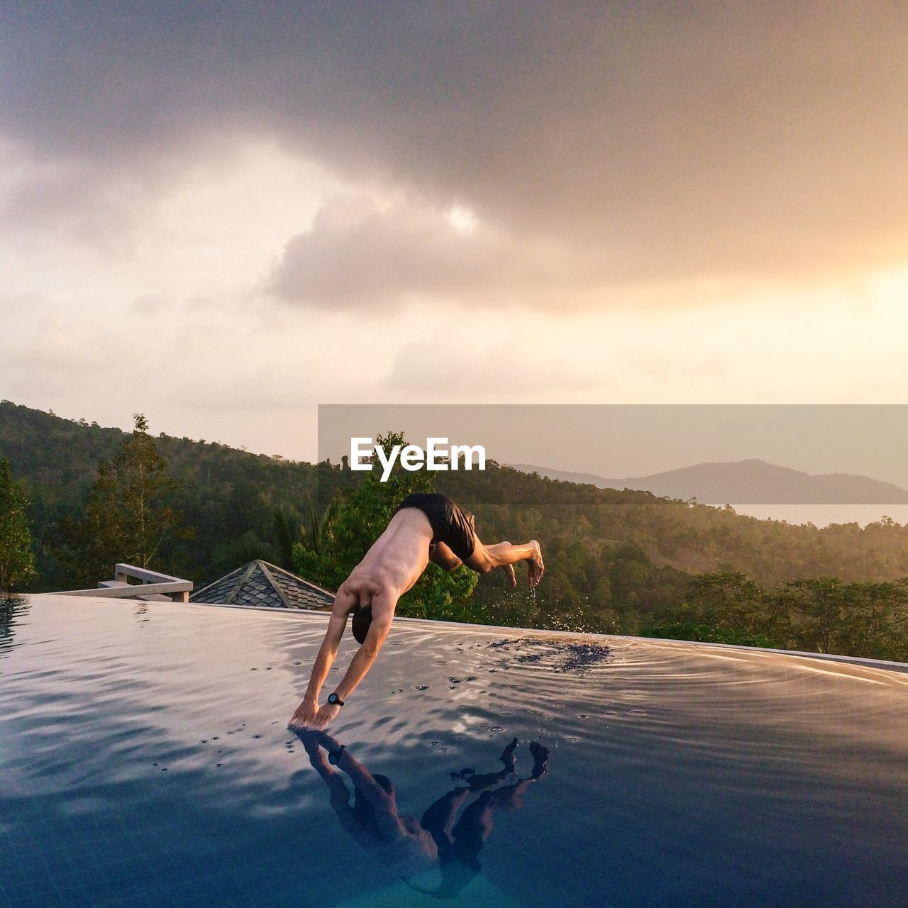 Shirtless man diving into swimming pool against sky during sunset