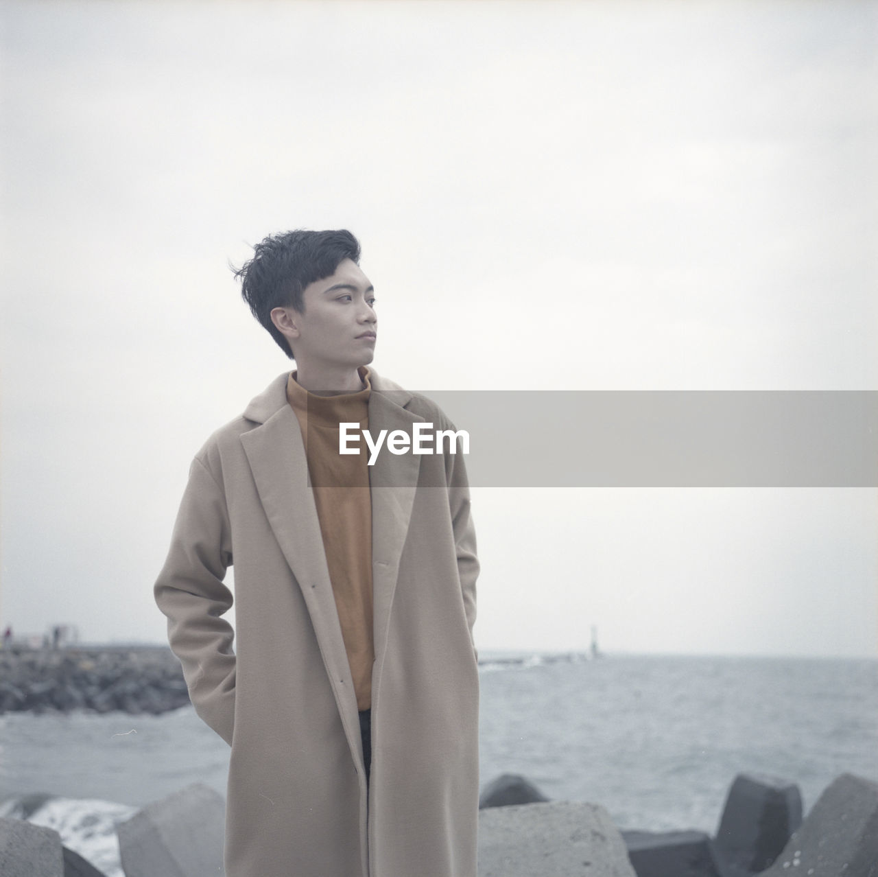 Thoughtful Young Man With Hands In Pockets Looking Away While Standing At Beach Against Sky
