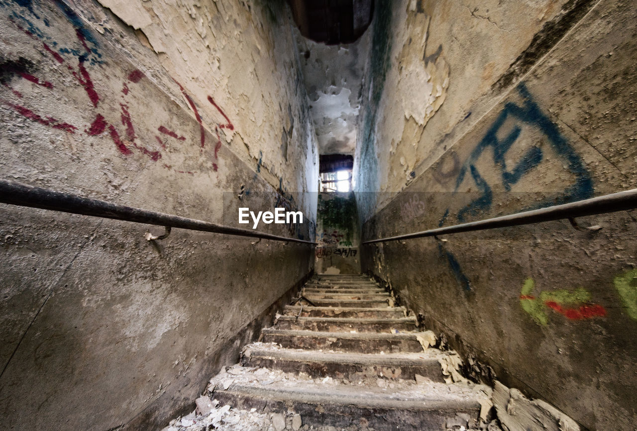 architecture, staircase, steps and staircases, built structure, wall - building feature, direction, building, the way forward, building exterior, no people, railing, narrow, day, old, outdoors, wall, graffiti, low angle view, weathered, alley