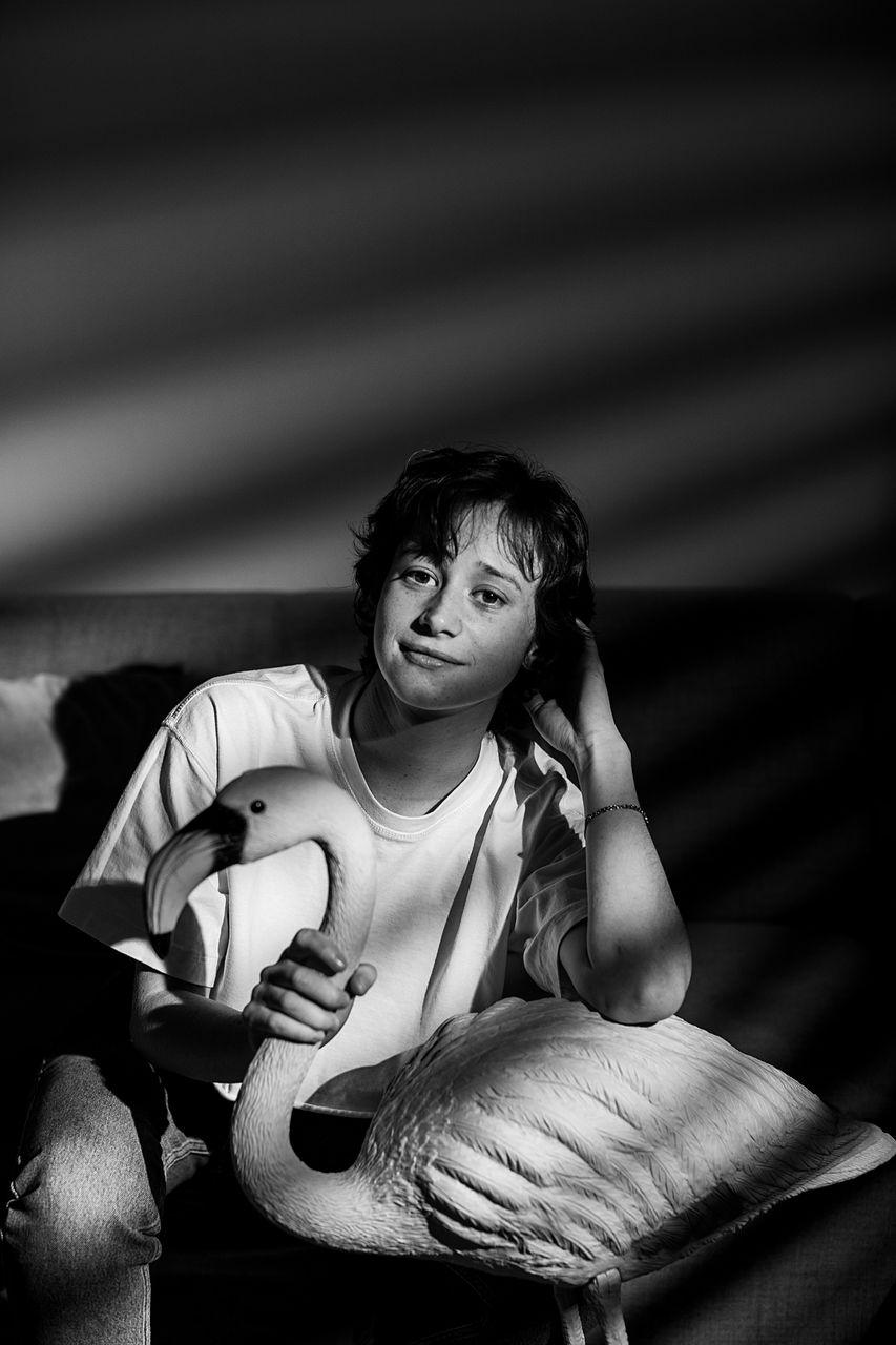 Portrait of smiling woman holding flamingo sculpture in darkroom