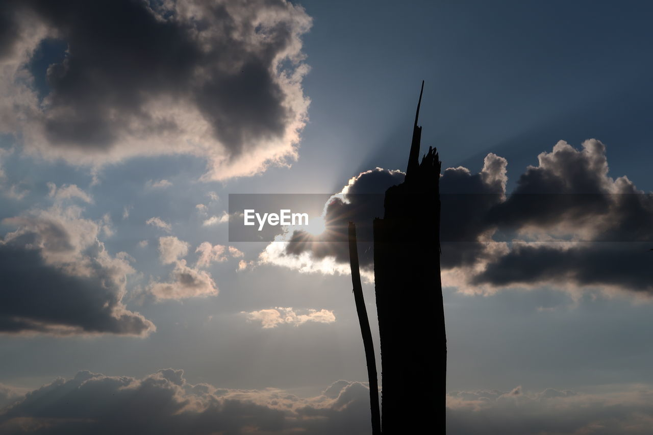 cloud - sky, sky, low angle view, silhouette, no people, sunlight, nature, sunset, sunbeam, outdoors, pole, built structure, back lit, day, sun, architecture, building exterior, lens flare, flag, beauty in nature, pollution