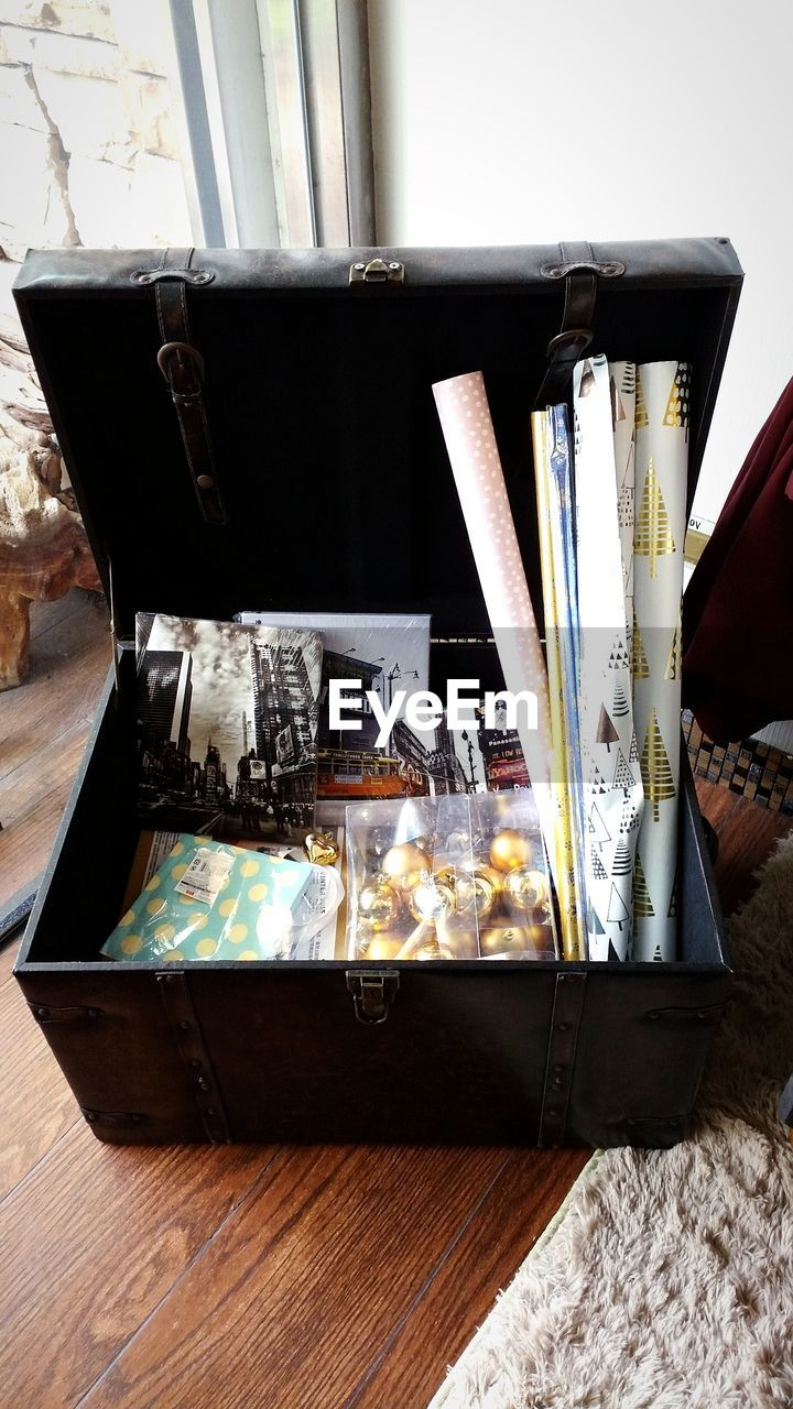 High Angle View Of Books And Decorations On Luggage On Floorboard