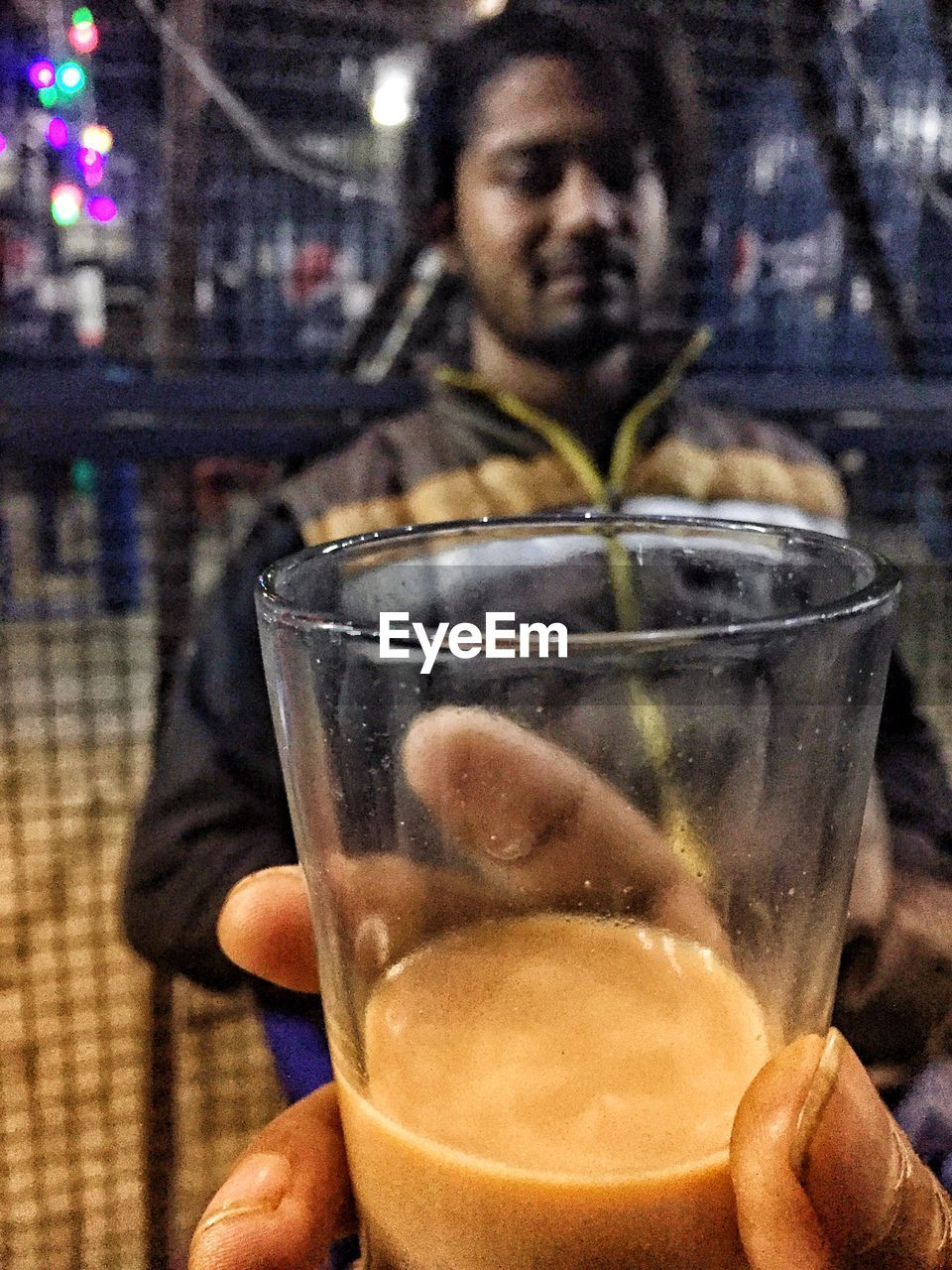 drink, real people, food and drink, holding, alcohol, focus on foreground, refreshment, drinking glass, leisure activity, lifestyles, human hand, men, night, one person, human body part, close-up, outdoors, illuminated, freshness, city, adult, people, adults only
