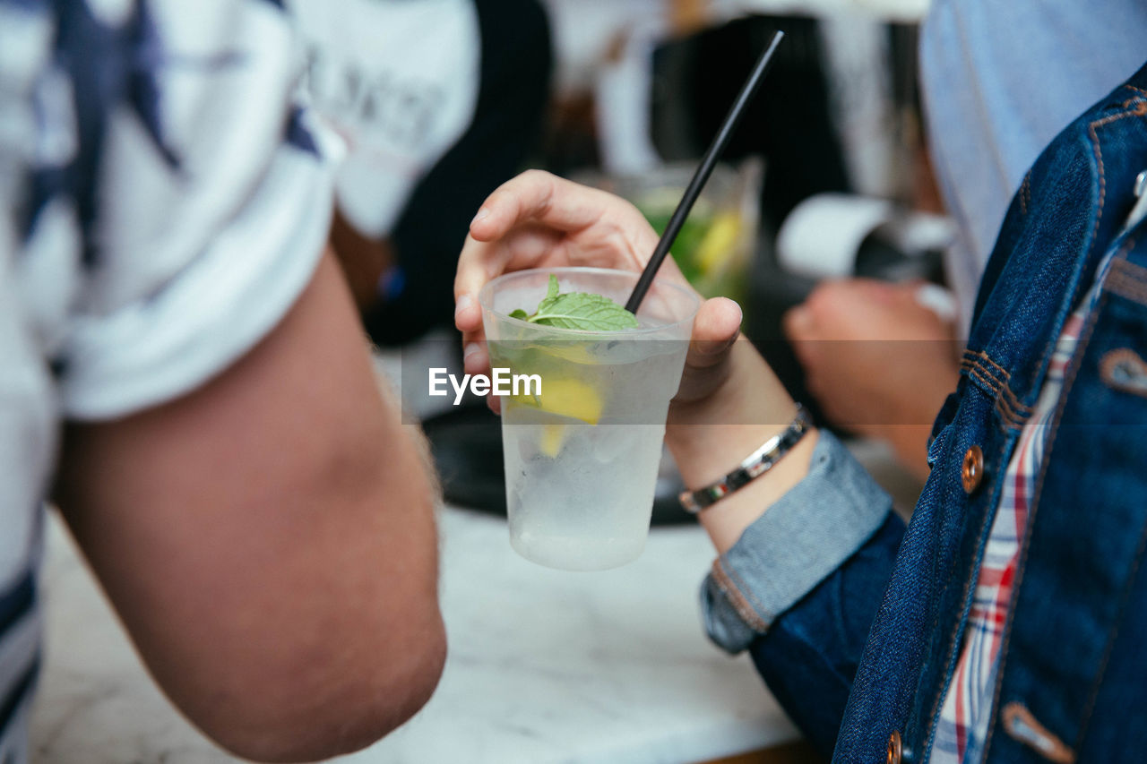 drink, refreshment, food and drink, holding, straw, drinking straw, real people, focus on foreground, midsection, freshness, food, household equipment, leisure activity, drinking glass, lifestyles, men, glass, hand, alcohol, people, cocktail, outdoors, drinking